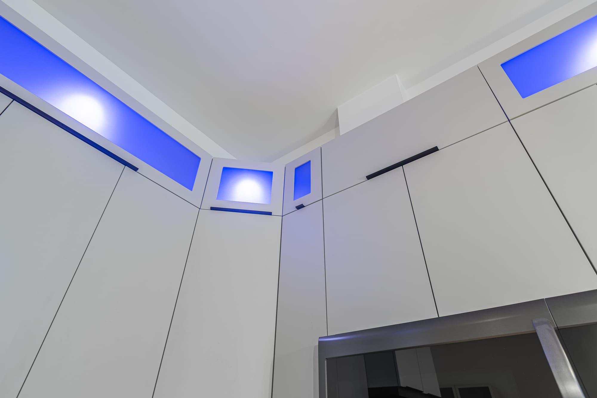 armoires de cuisine moderne blanches avec panneaux vitrés dans le haut et éclairage bleu