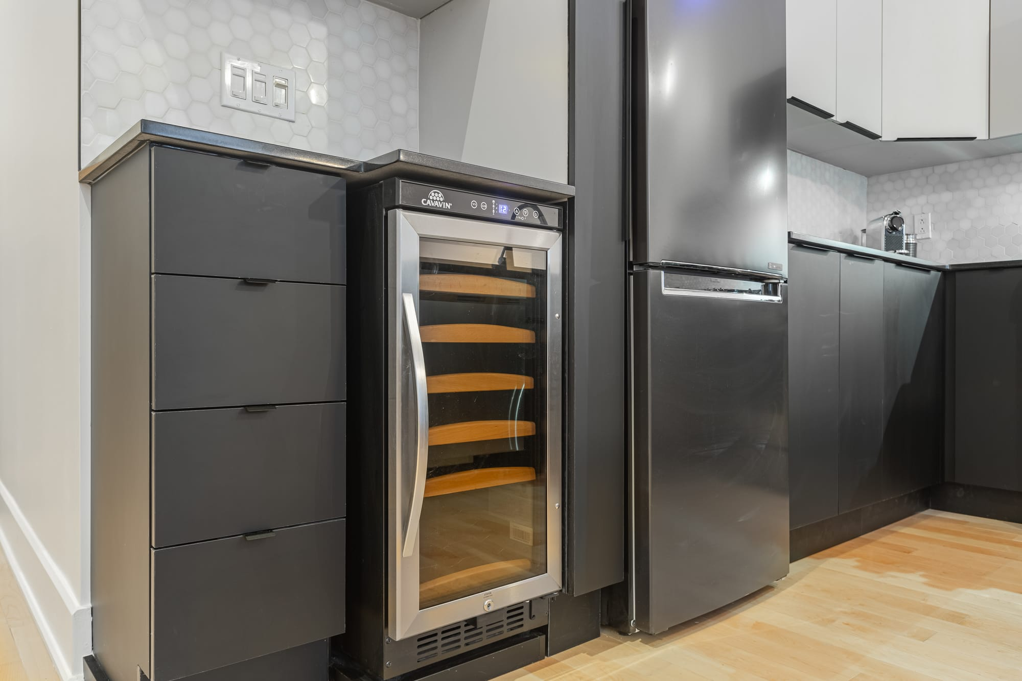 cellier avec réfrigérateur gris foncé dans une cuisine moderne deux tons rénovée