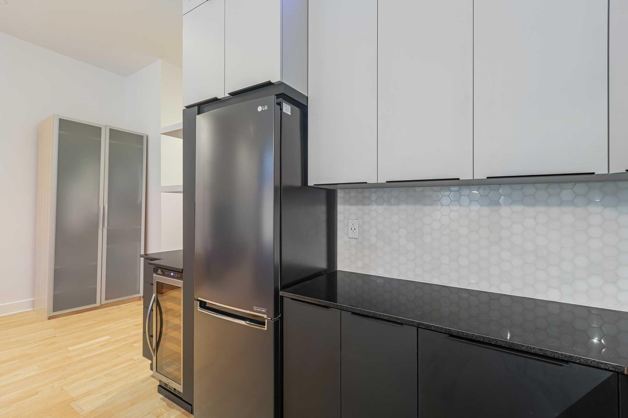 comptoir de cuisine noir avec réfrigérateur gris foncé, cellier et armoires blanches