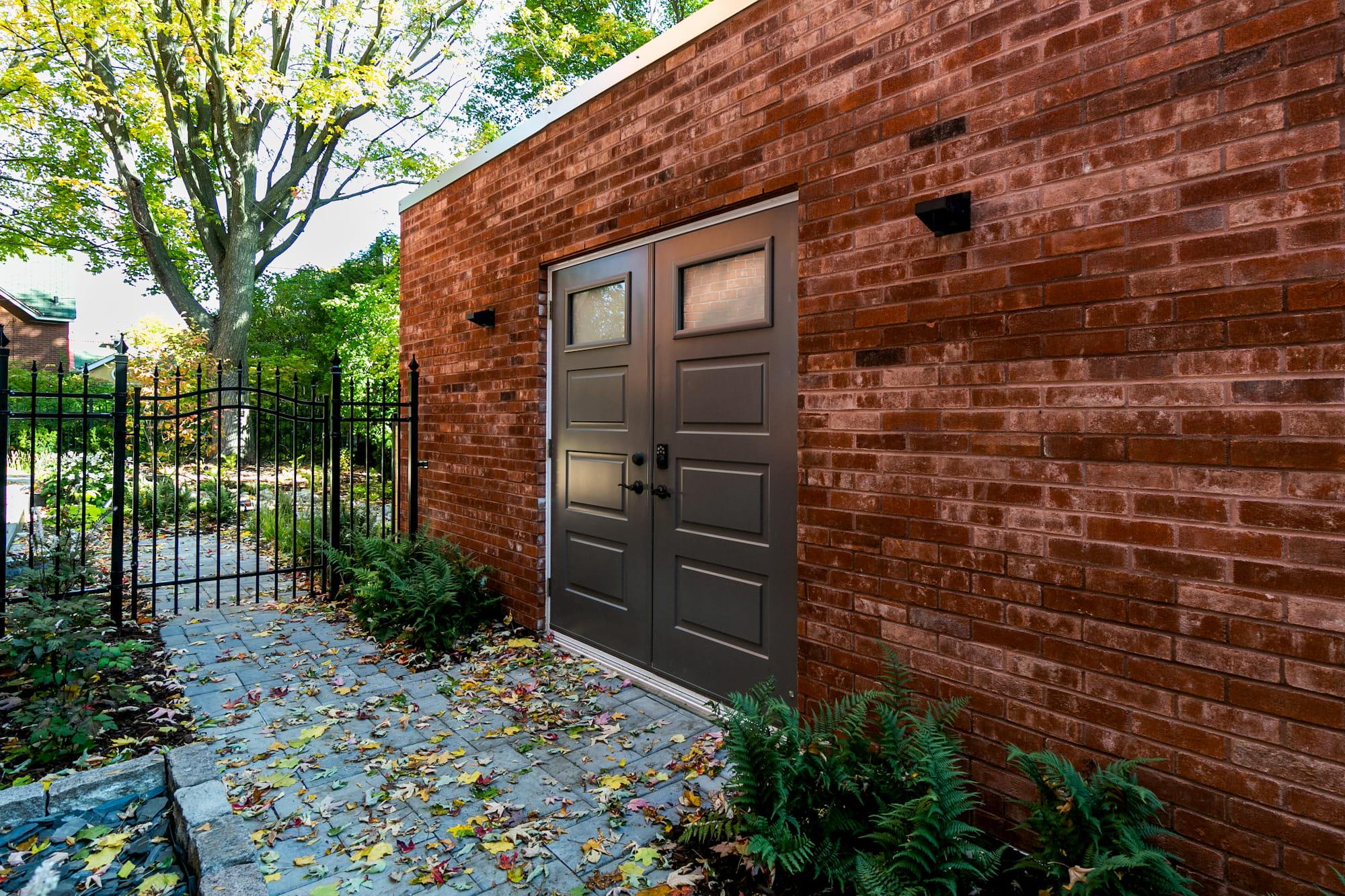 vue de côté d'une construction de garage en brique avec 2 portes