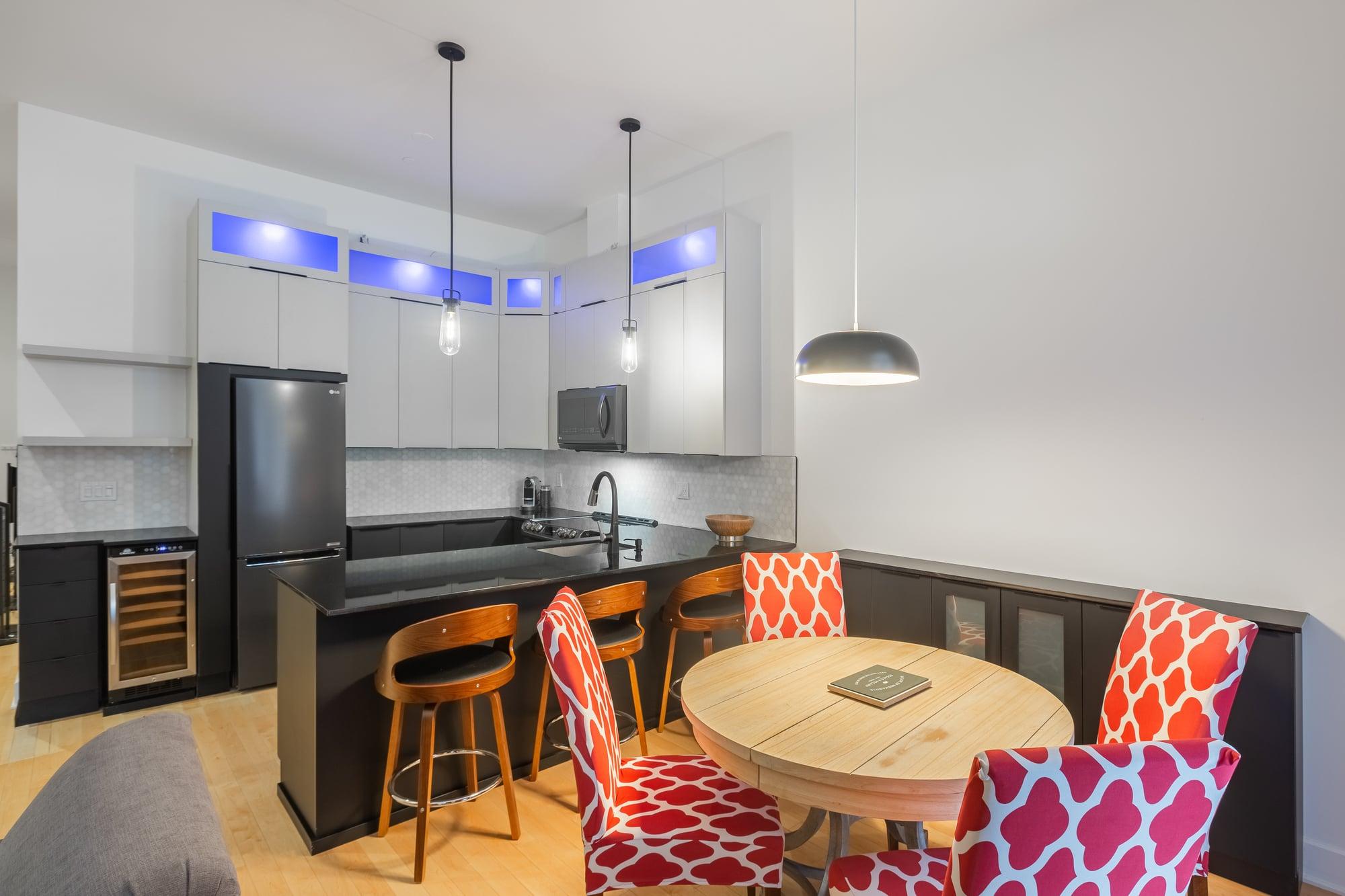 cuisine contemporaine avec armoires deux tons, comptoir noir et table avec 4 chaises