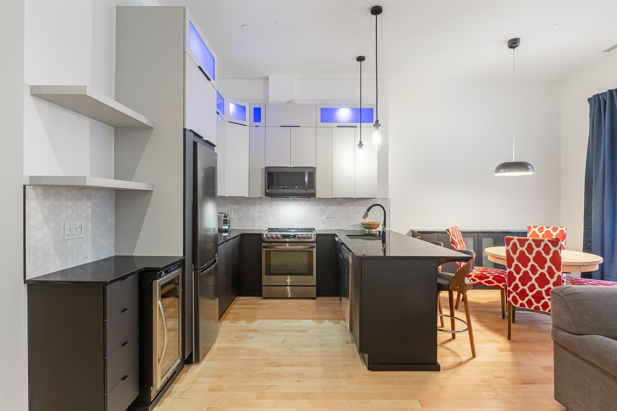 cuisine moderne nouvellement rénovée avec armoires deux tons blanches et grises foncées + comptoir noir