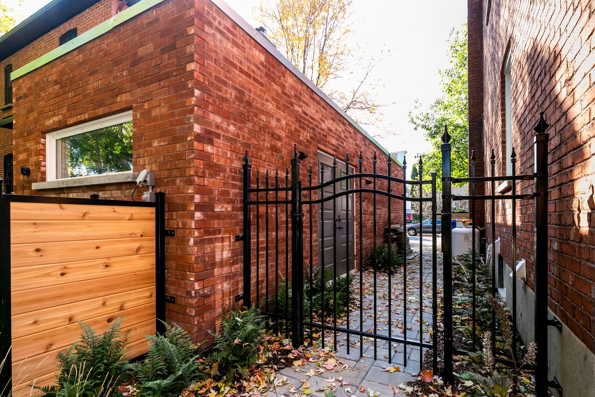 constructin de garage simple en brique rouge vue de côté avec clôture noire