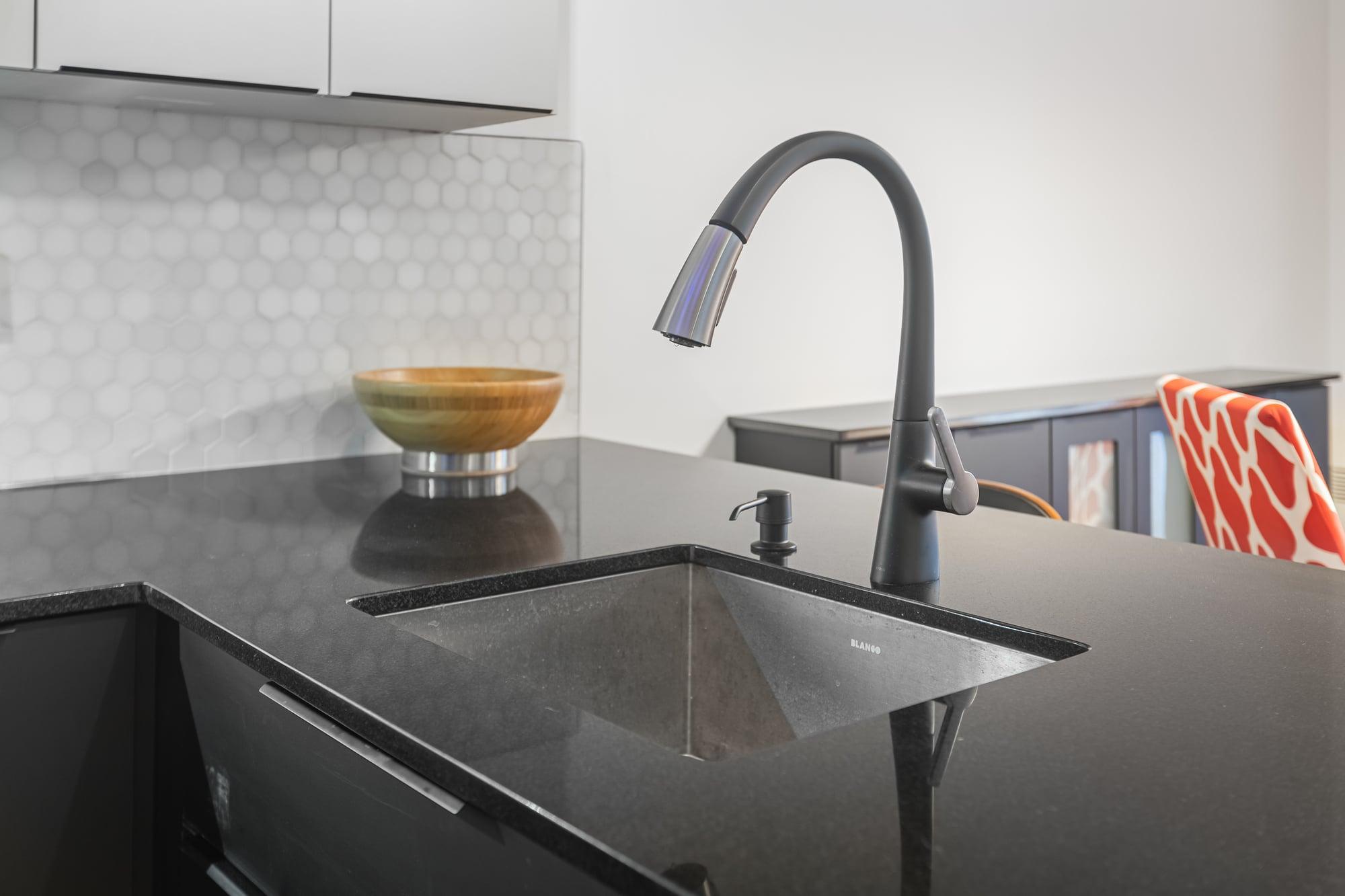 robinet de cuisine avec lavabo carré intégré dans comptoir noir