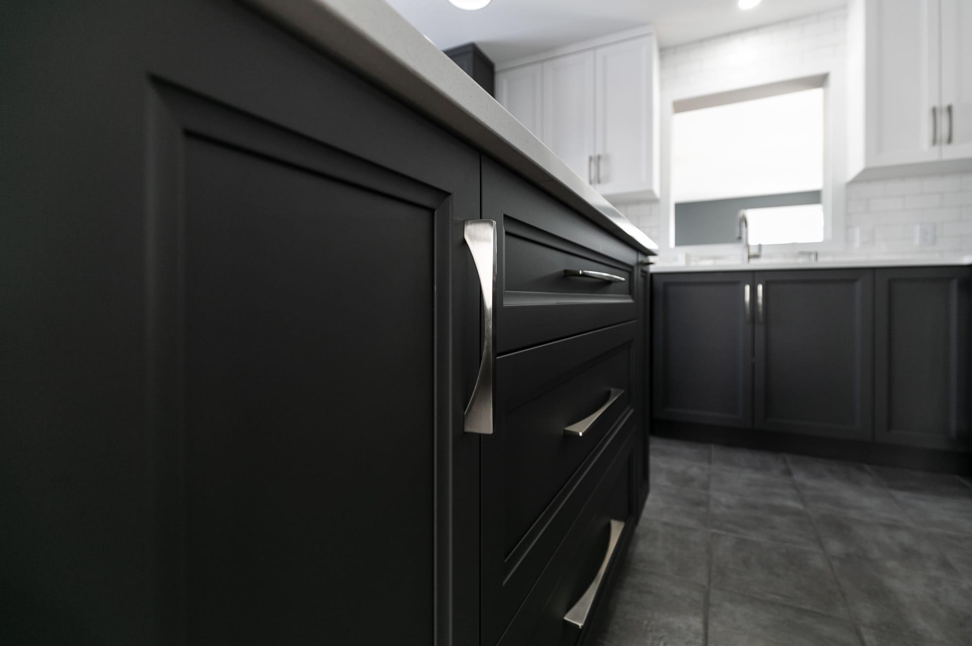 armoires de cuisine deux tons grises et blanches avec comptoir en quartz et poignées en stainless