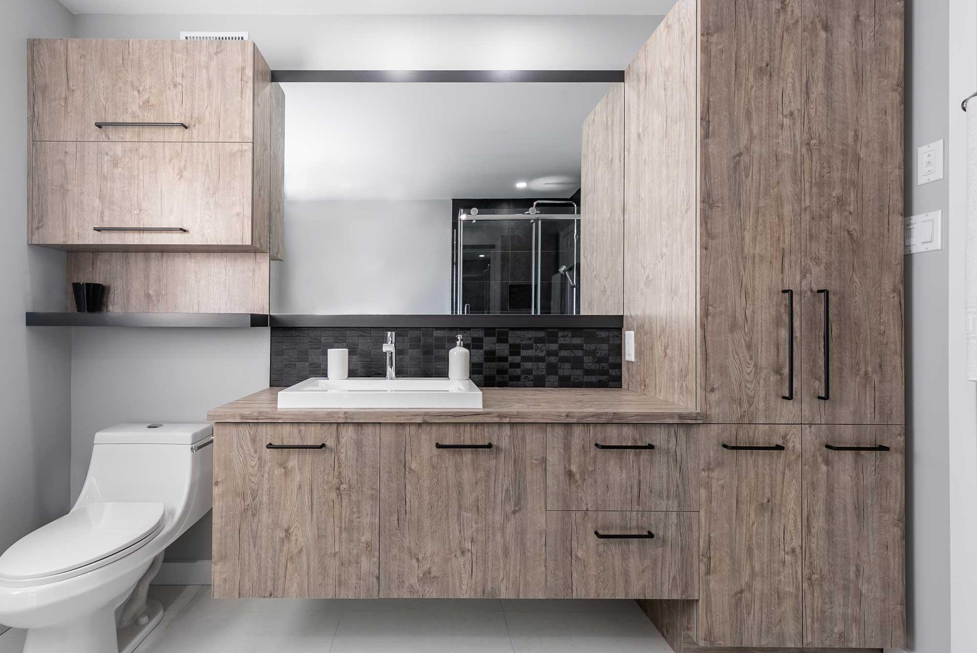 armoires de salle de bain beiges avec poignées noires et grand miroir
