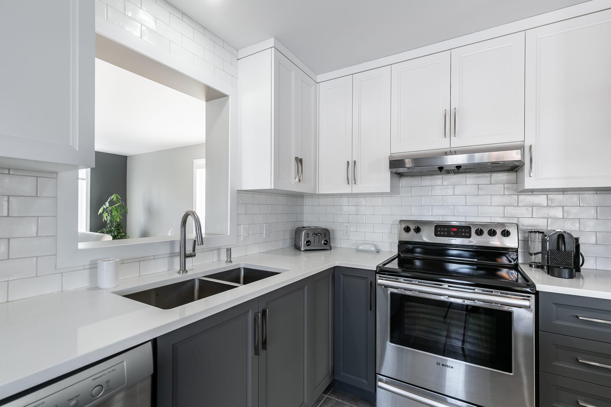 cuisine contemporaine grise et blanche avec cuisinière en stainless