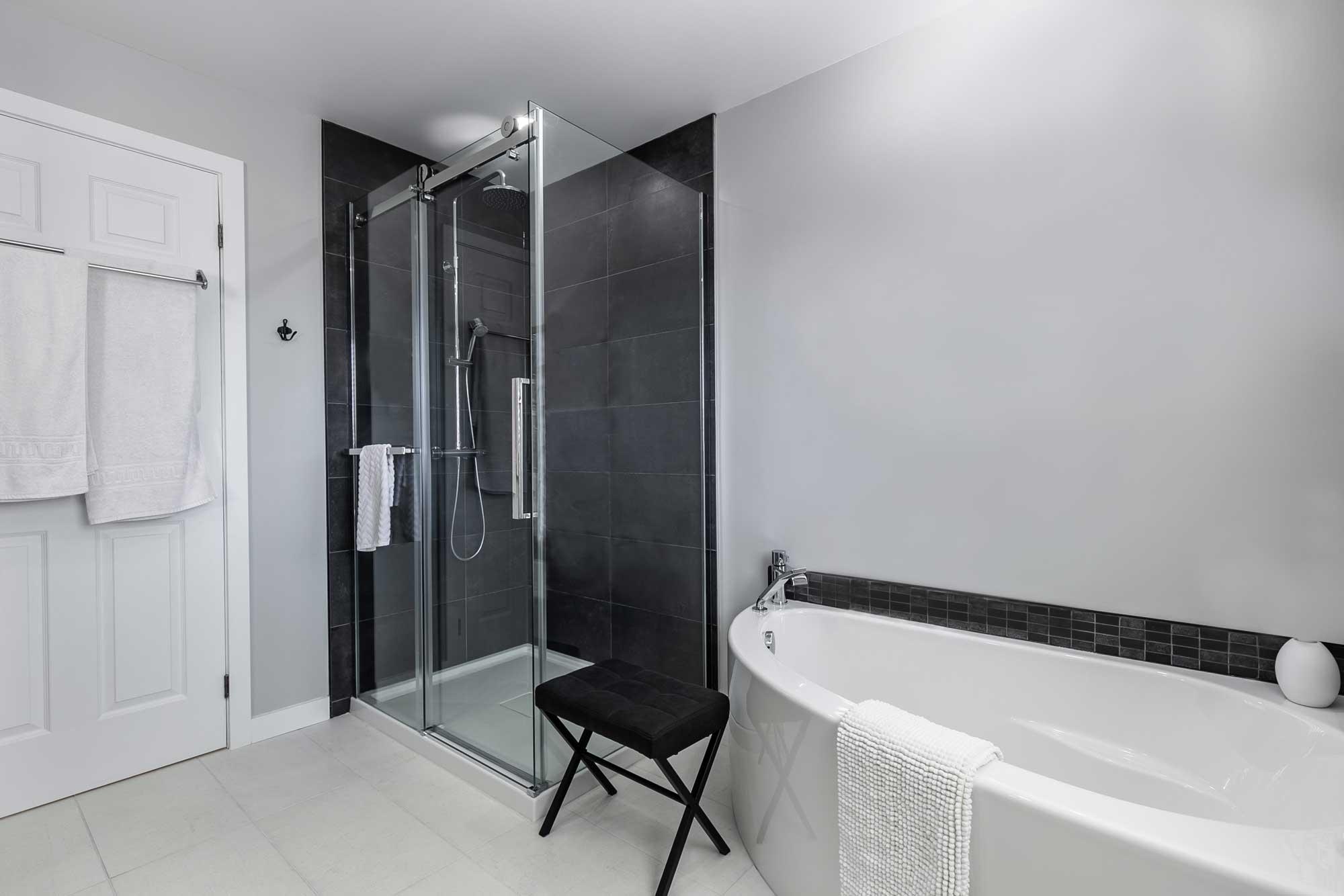 déco de salle de bain avec banc noir, douche vitrée et bain autoportant