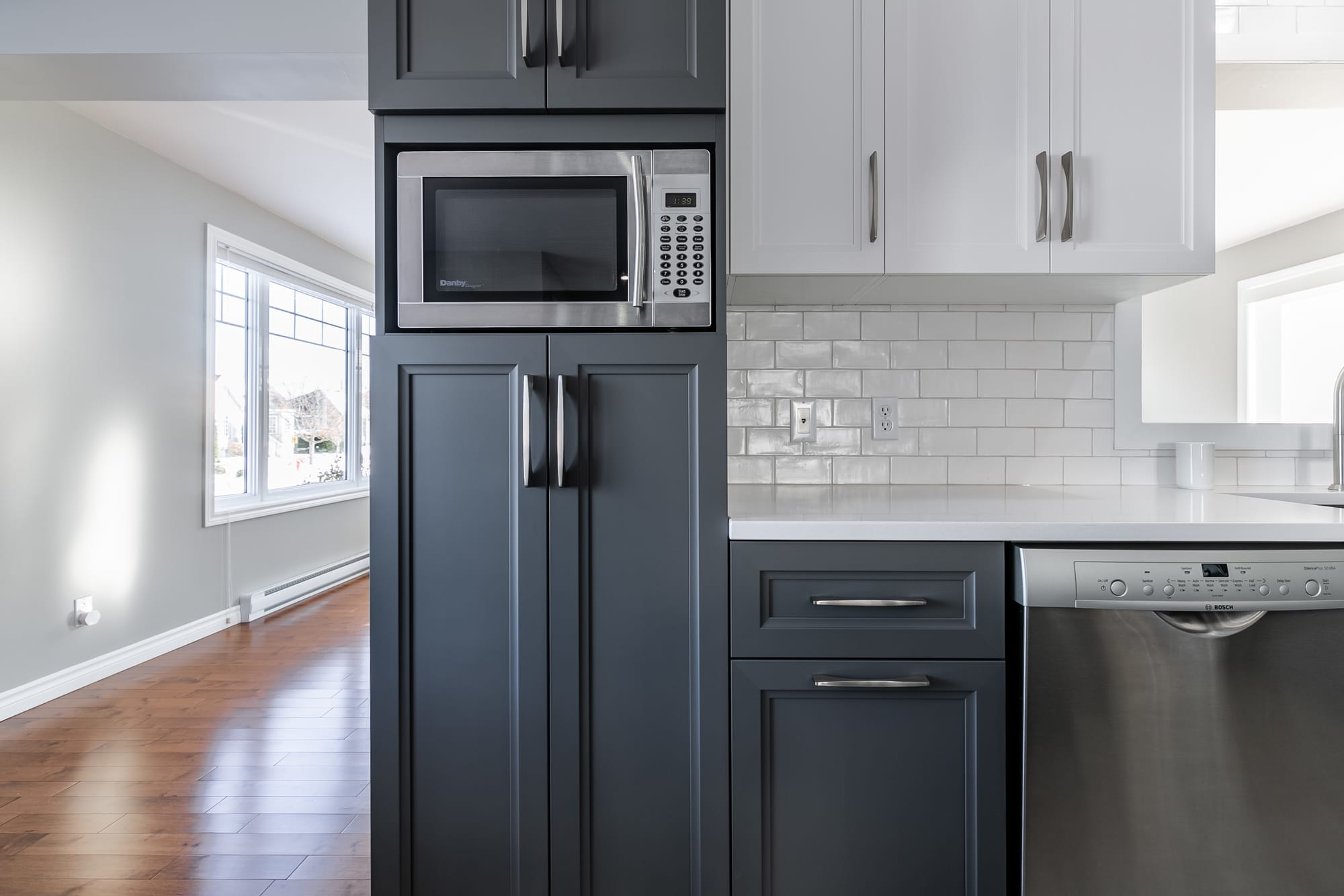 kitchen cabinets with microwaves and white backsplash