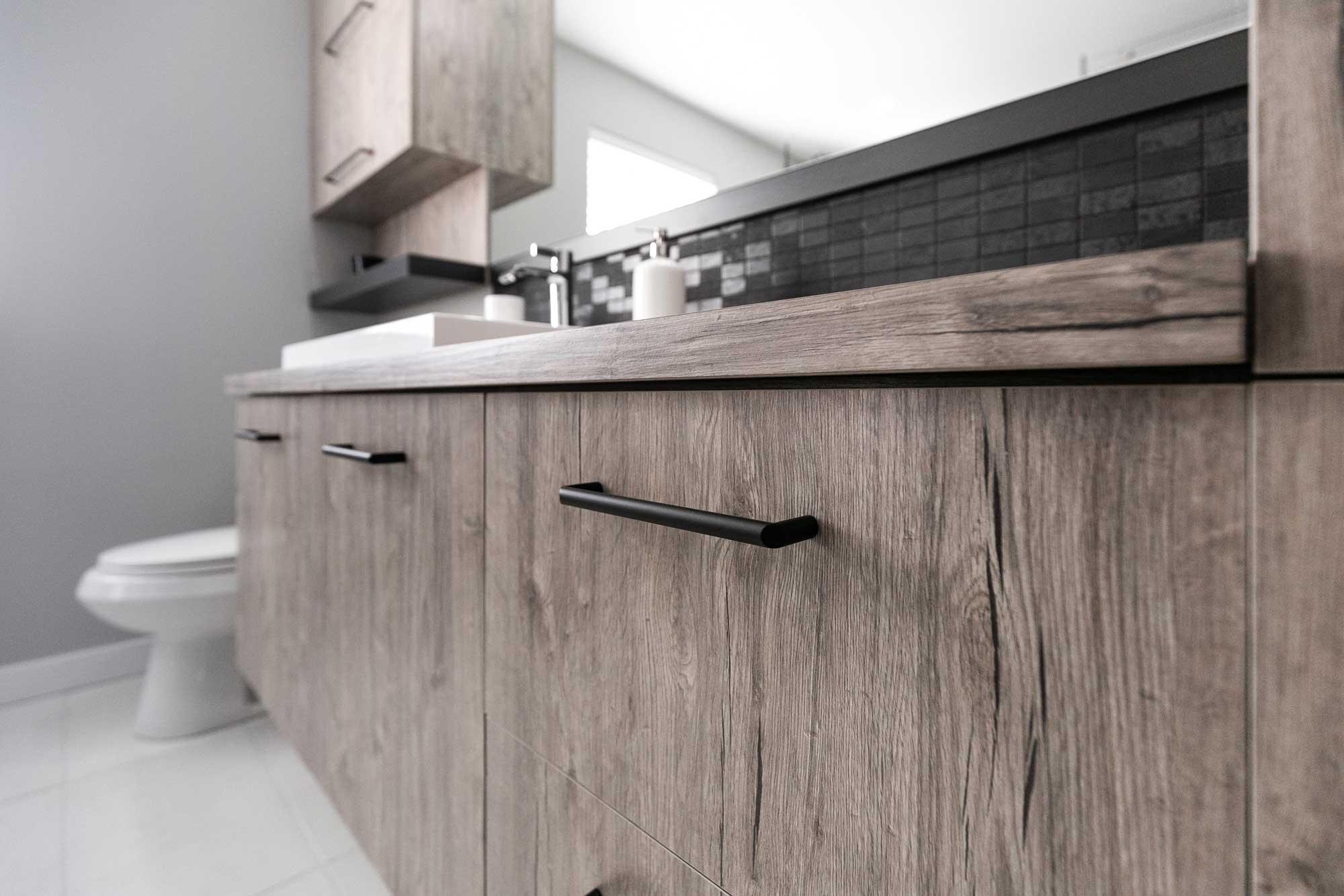salle de bain contemporaine avec armoire en bois beige et poignées noires