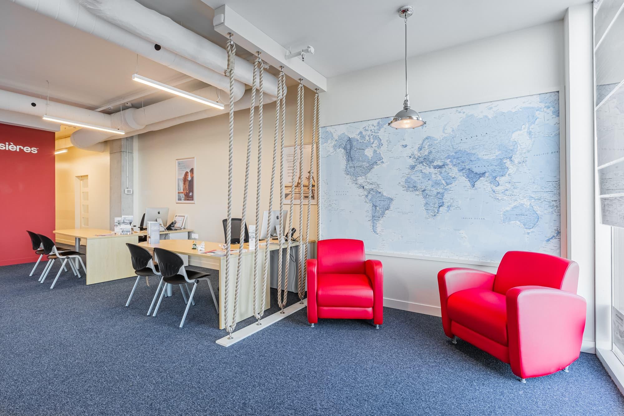 aménagement bureaux avec mur de cordes, carte du monde géante et fauteuils rouges