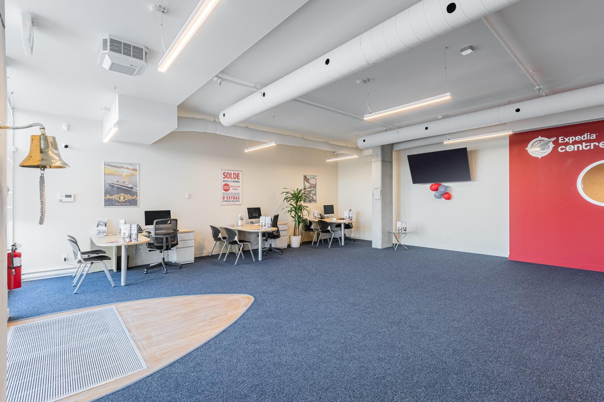 aménagement locaux d'un Expédia Centre de Croisières avec tapis bleu et mur rouge