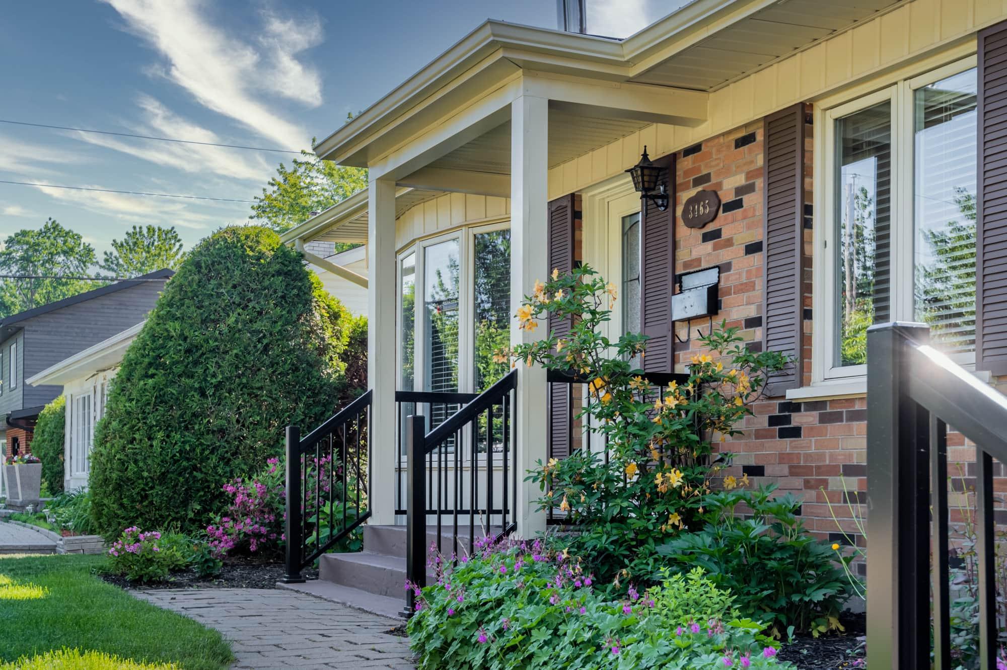 galerie avant d'une maison en briques beige et brune avec petit toit et rampes en aluminium
