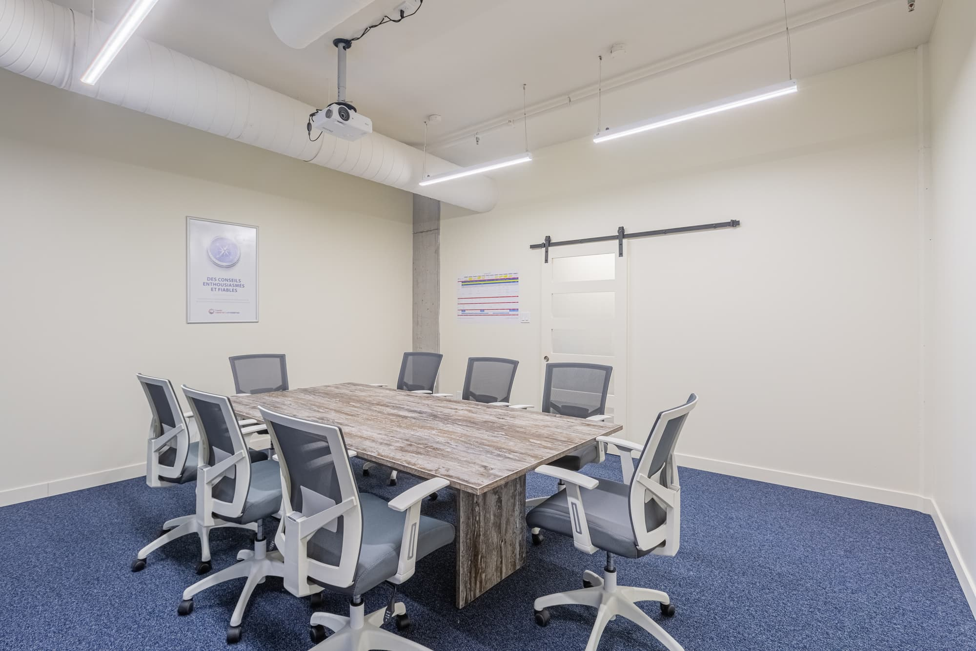meeting room with blue carpet, wooden table and 8 chairs