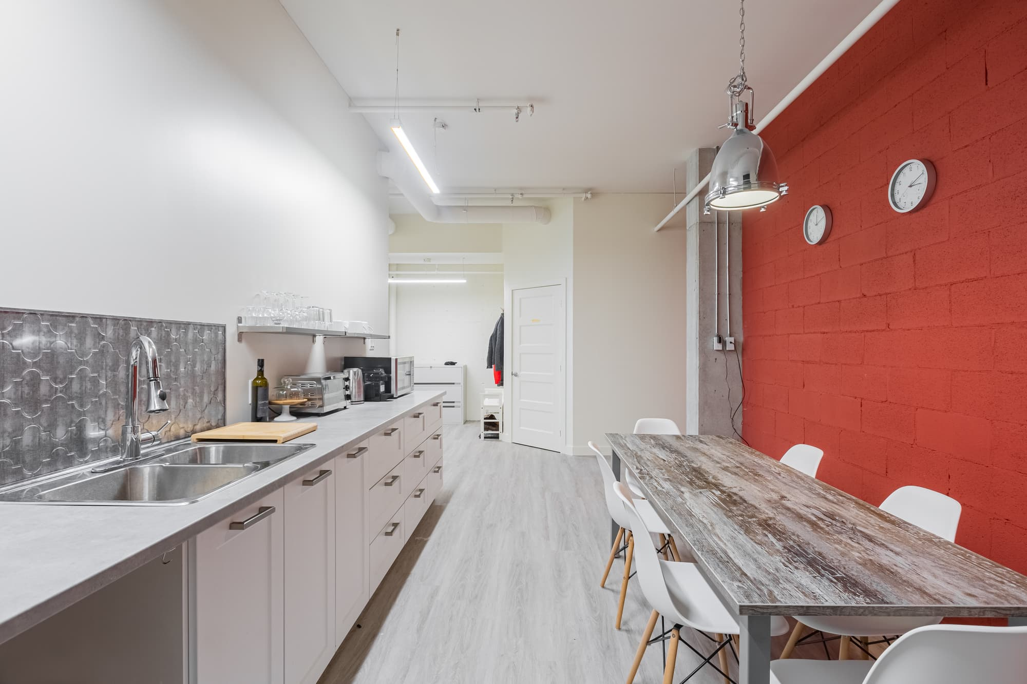 office kitchen with red wall, portholes, counter, etc.