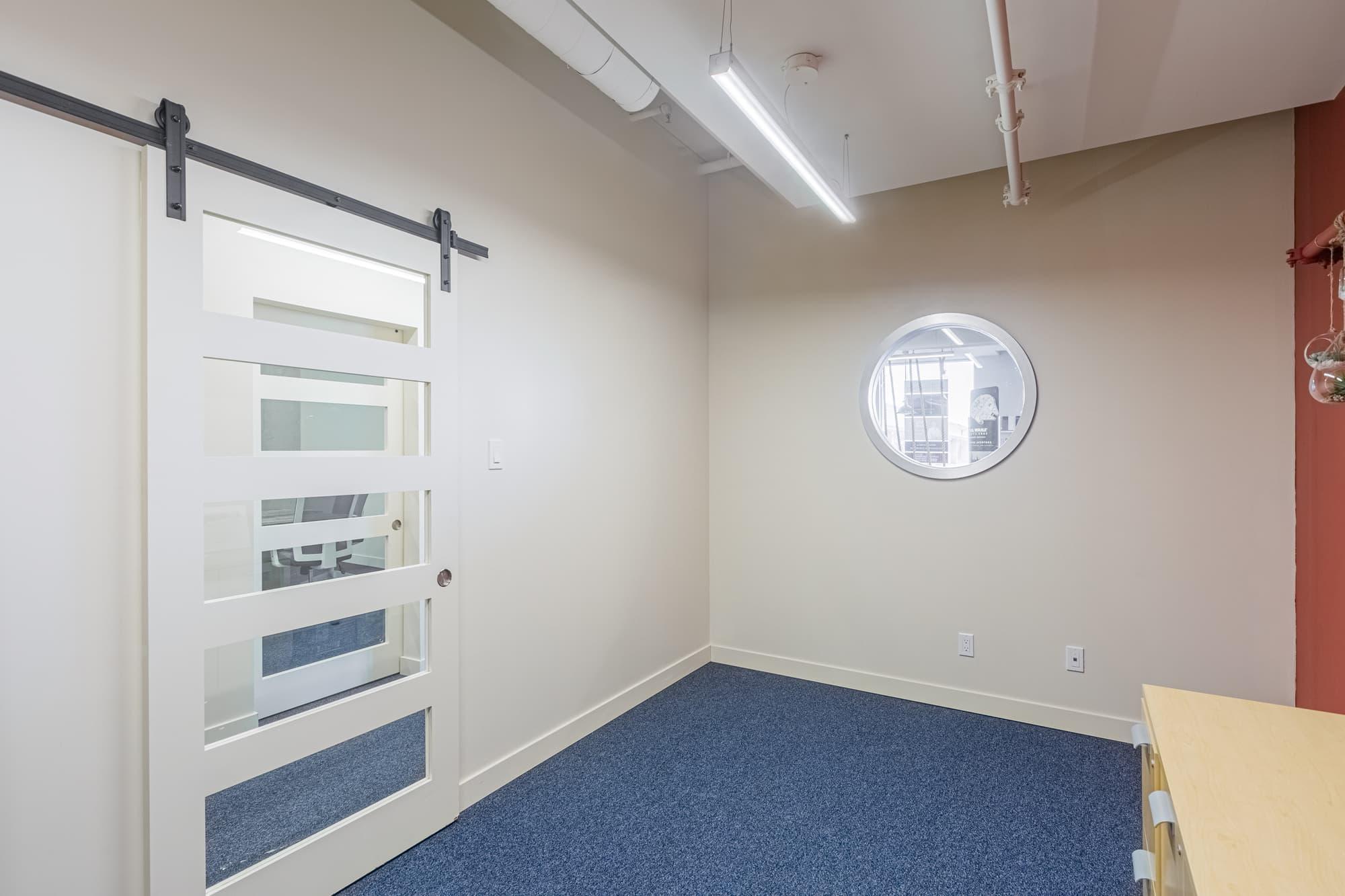 rénovation commerciale avec tapis bleu et porte coulissante en bois