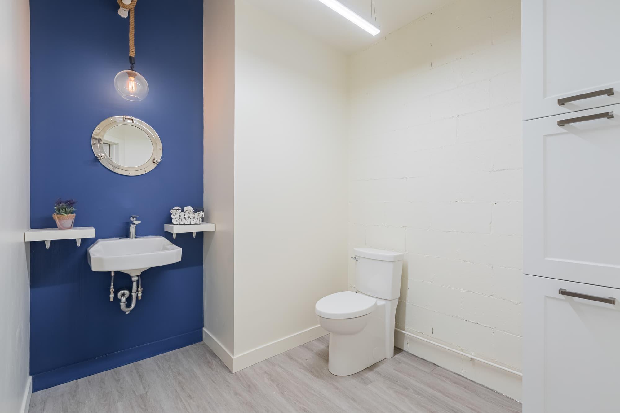 salle de bain entreprise avec mur bleu et lavabo suspendu