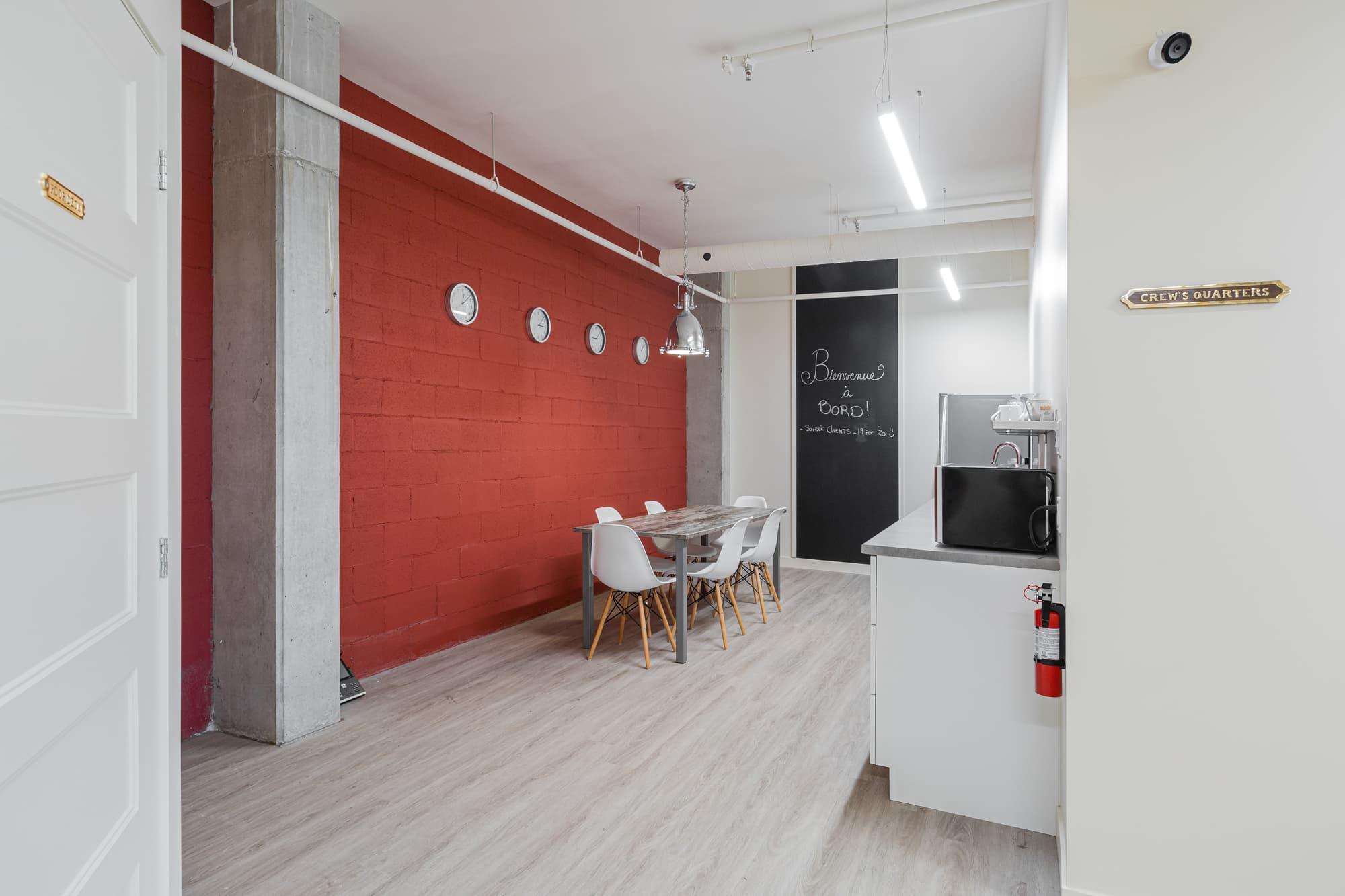 salle de pause pour employés avec mur rouge et hublots, table et chaises, comptoir, tableau noir, etc.