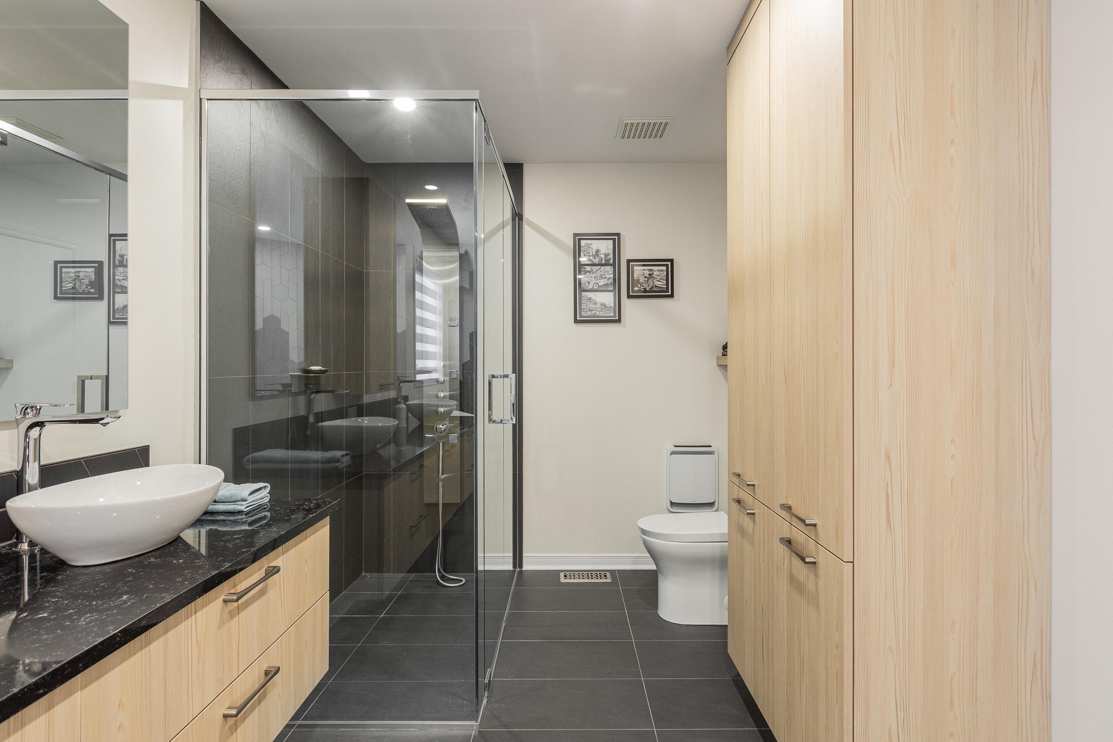 Grande cabine de douche vitrée avec vanité et lingerie en bois clair