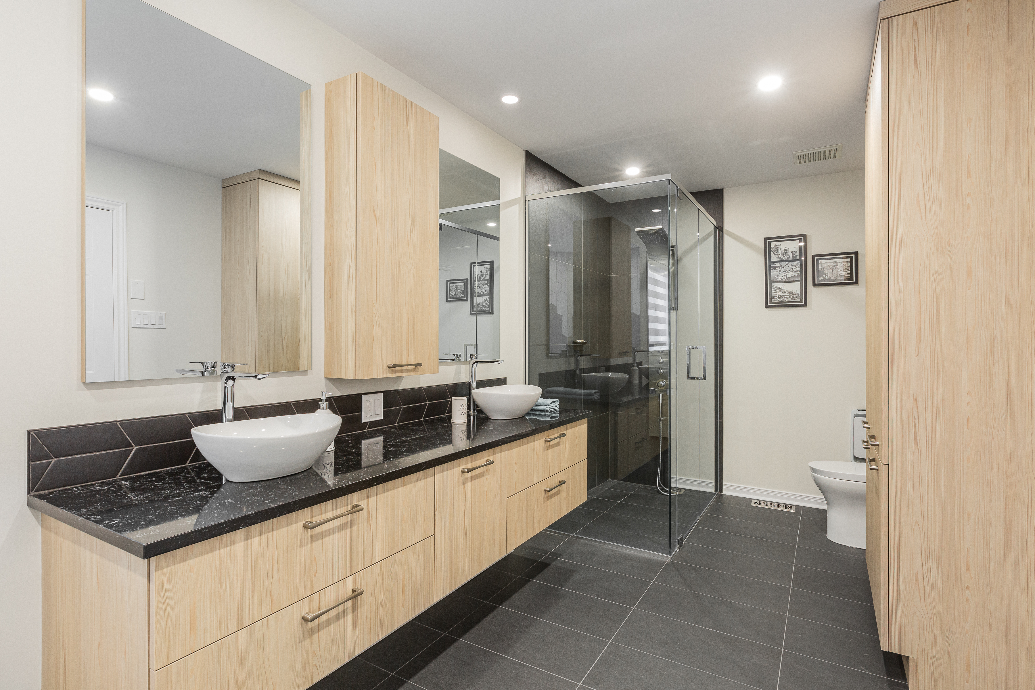 double sink with black counter, wooden cabinets and a glass shower