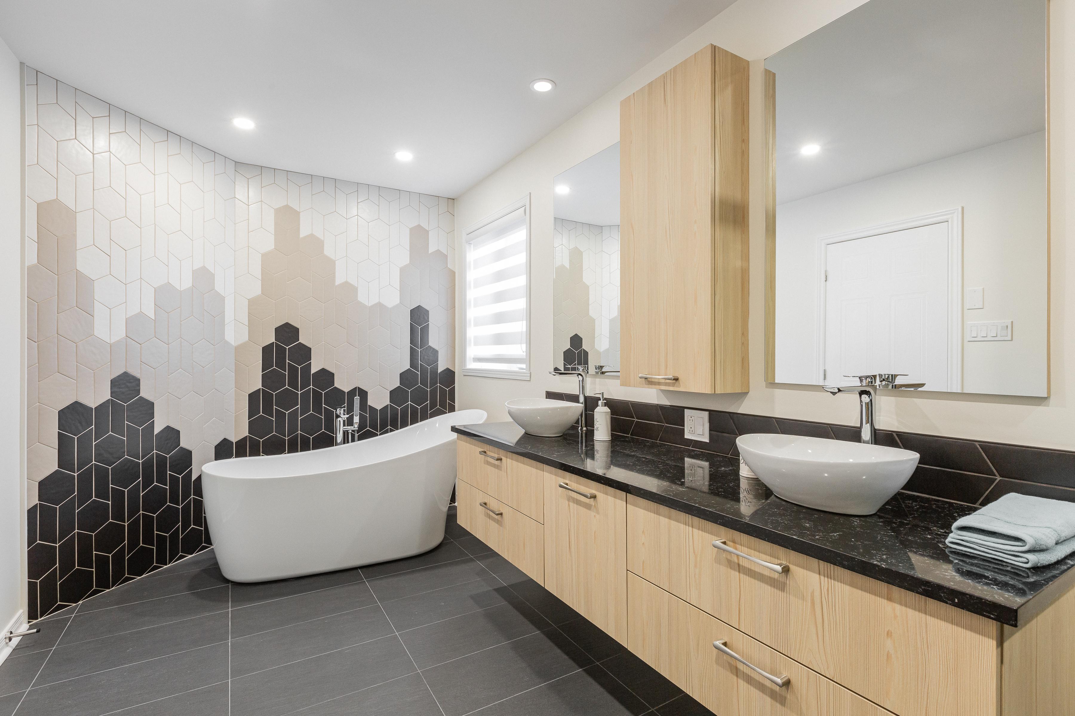 salle de bain rénovée de style moderne avec baignoire autoportante, mur de tuiles géométriques et grande vanité
