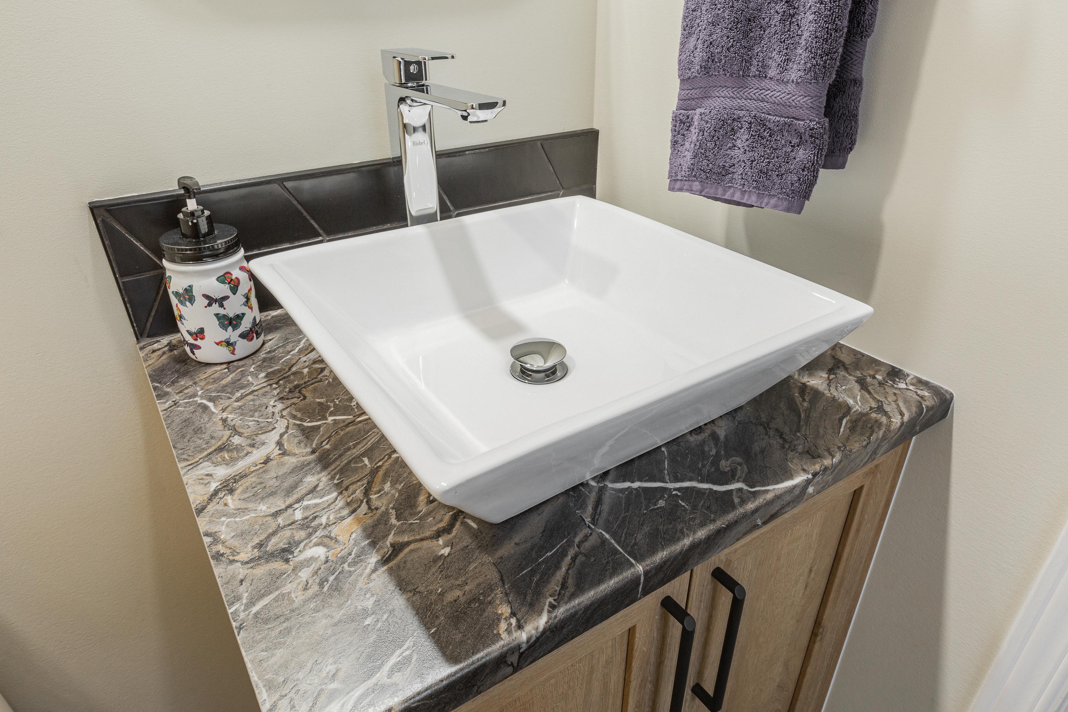 vasque rectangulaire et son comptoir en stratifié à l'effet marbre sur une petite vanité