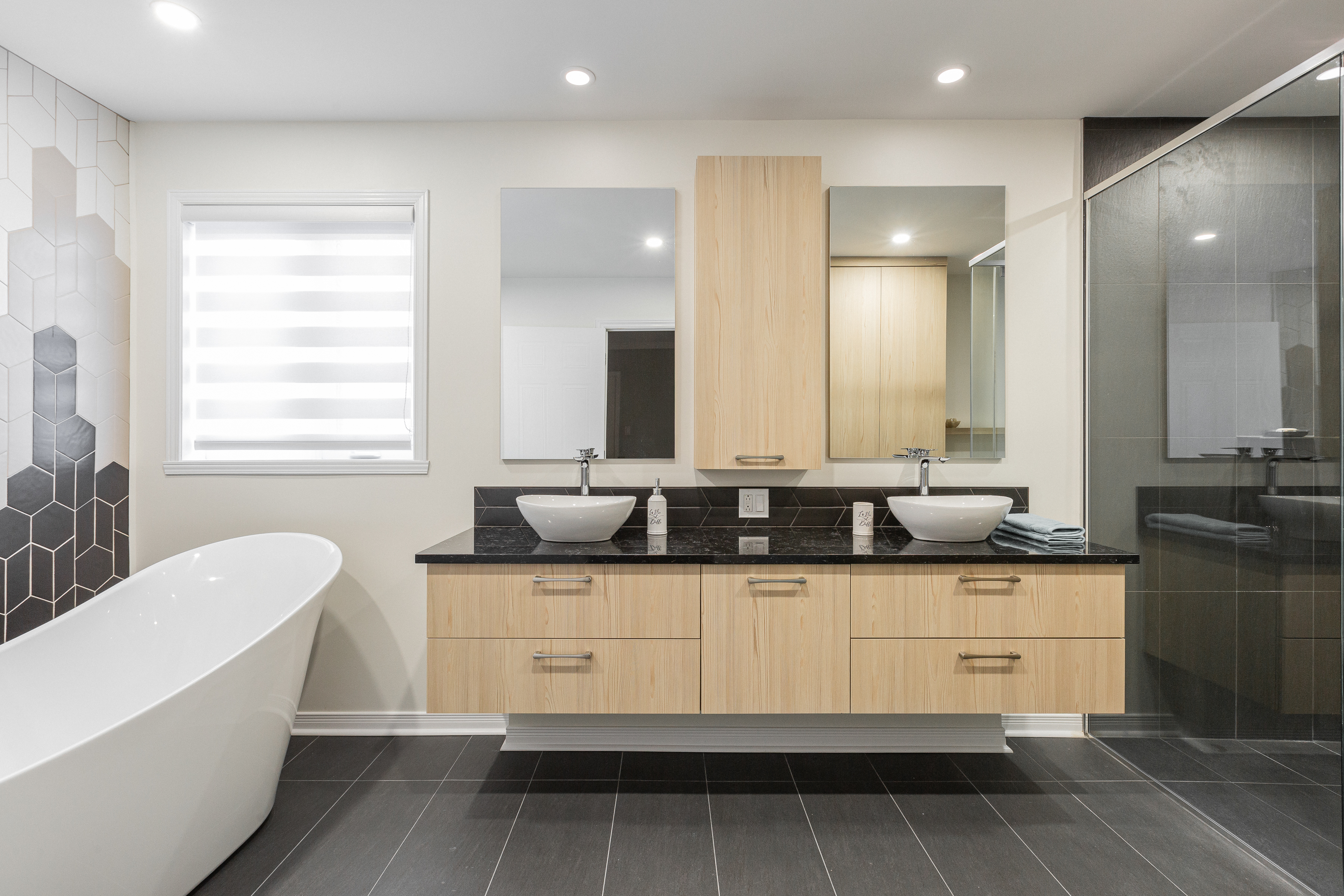 a spacious and trendy bathroom look with a freestanding bathtub and wooden cabinets