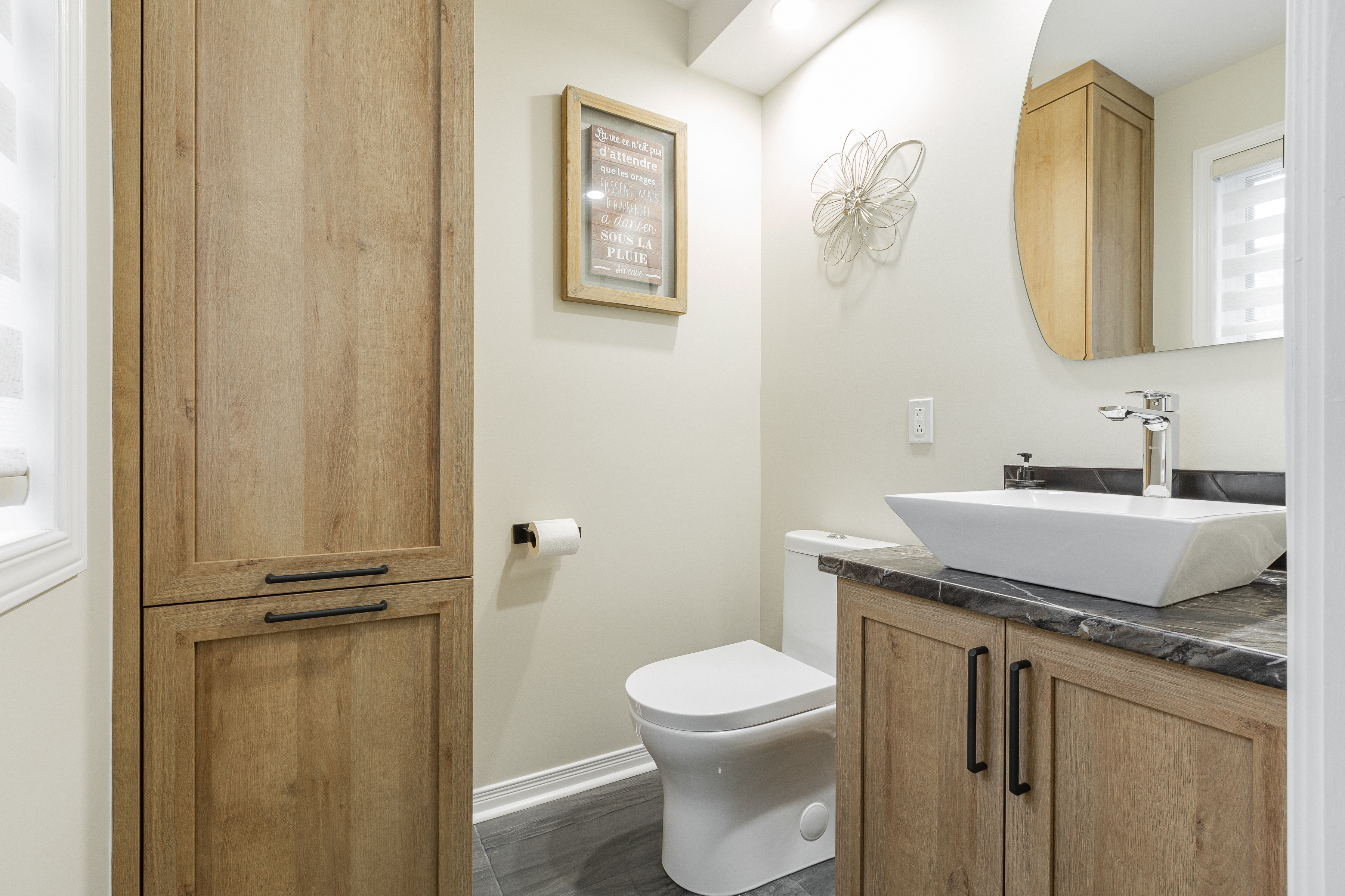 small powder room with wooden cabinets and light colored walls