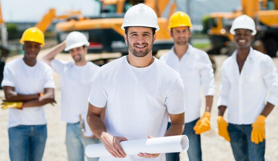 Groupe d'entrepreneurs en construction à l'extérieur portant des t-shirts blancs et des casques de construction
