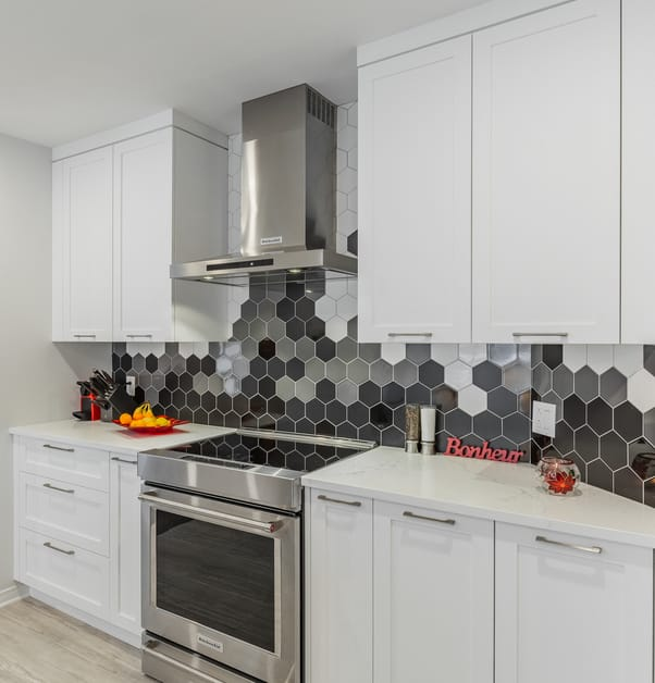 A kitchen with a stove, white shaker cabinets and a backsplash with modernhexagonaltiles