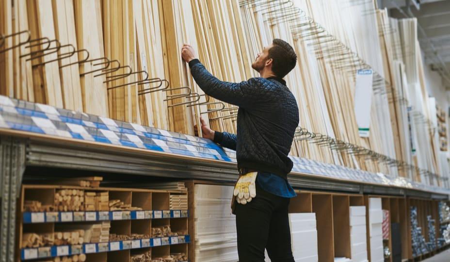charpentier sélectionnant des planches de bois dans un magasin de matériaux de construction