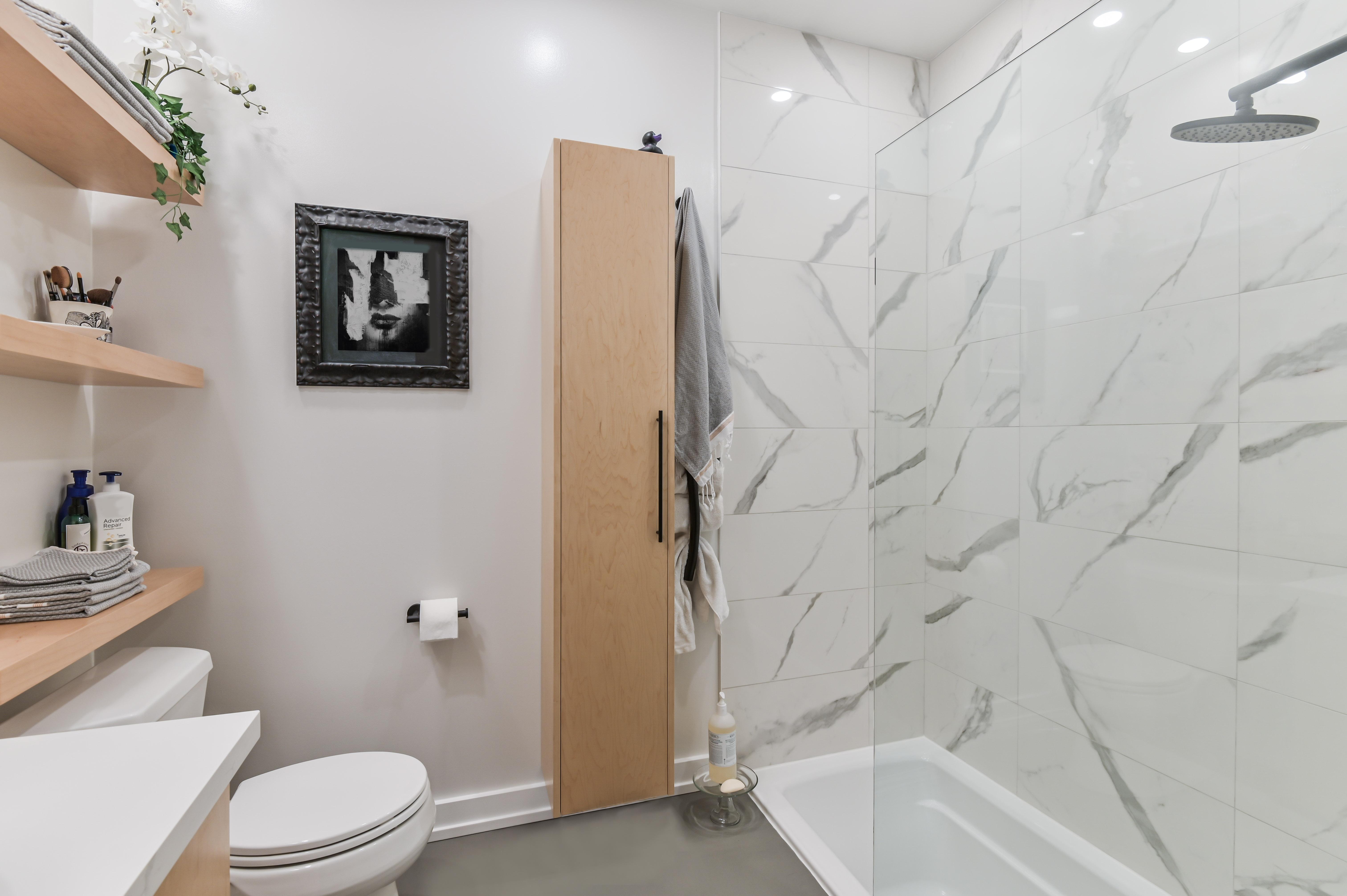 Petite salle de bain rénovée avec un mélange de tuiles imitation marbre et de microciment qui se marie bien au reste du décor
