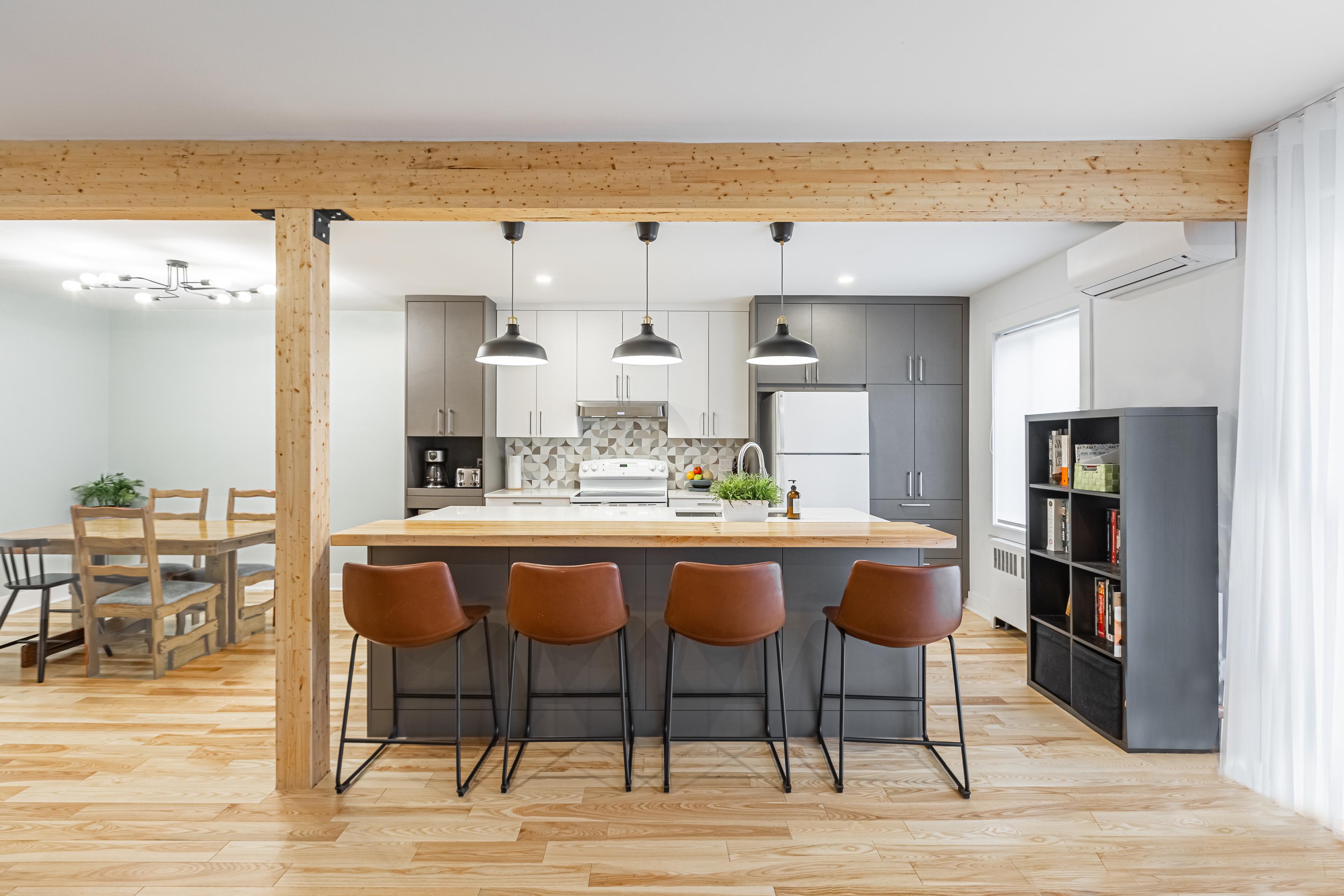 cuisine à aire ouverte avec comptoirs en quartz blanc avec une section en bois sur l'îlot