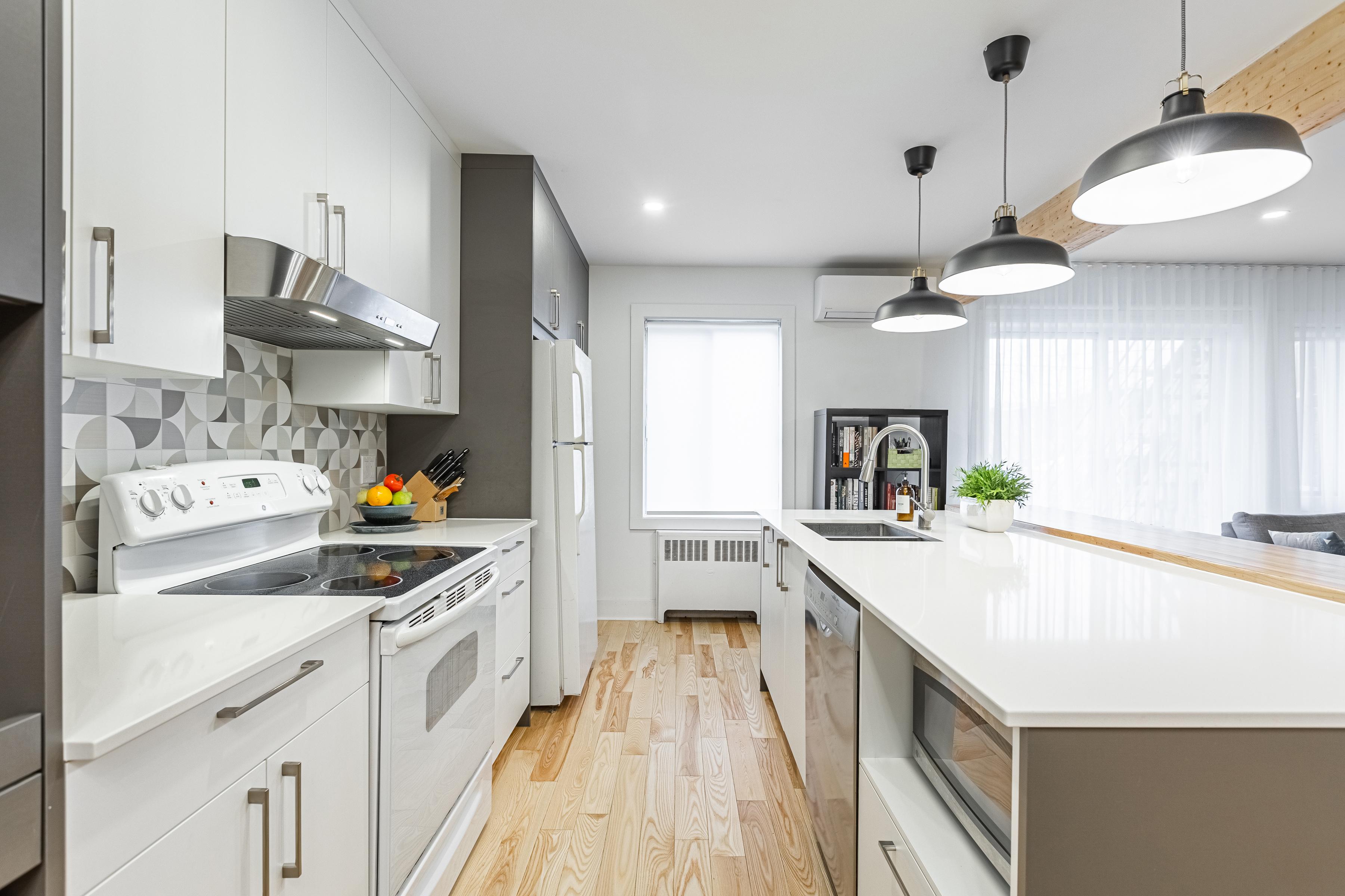 Cuisine à aire ouverte moderne avec armoires blanches et grises, îlot et comptoirs de quartz blancs