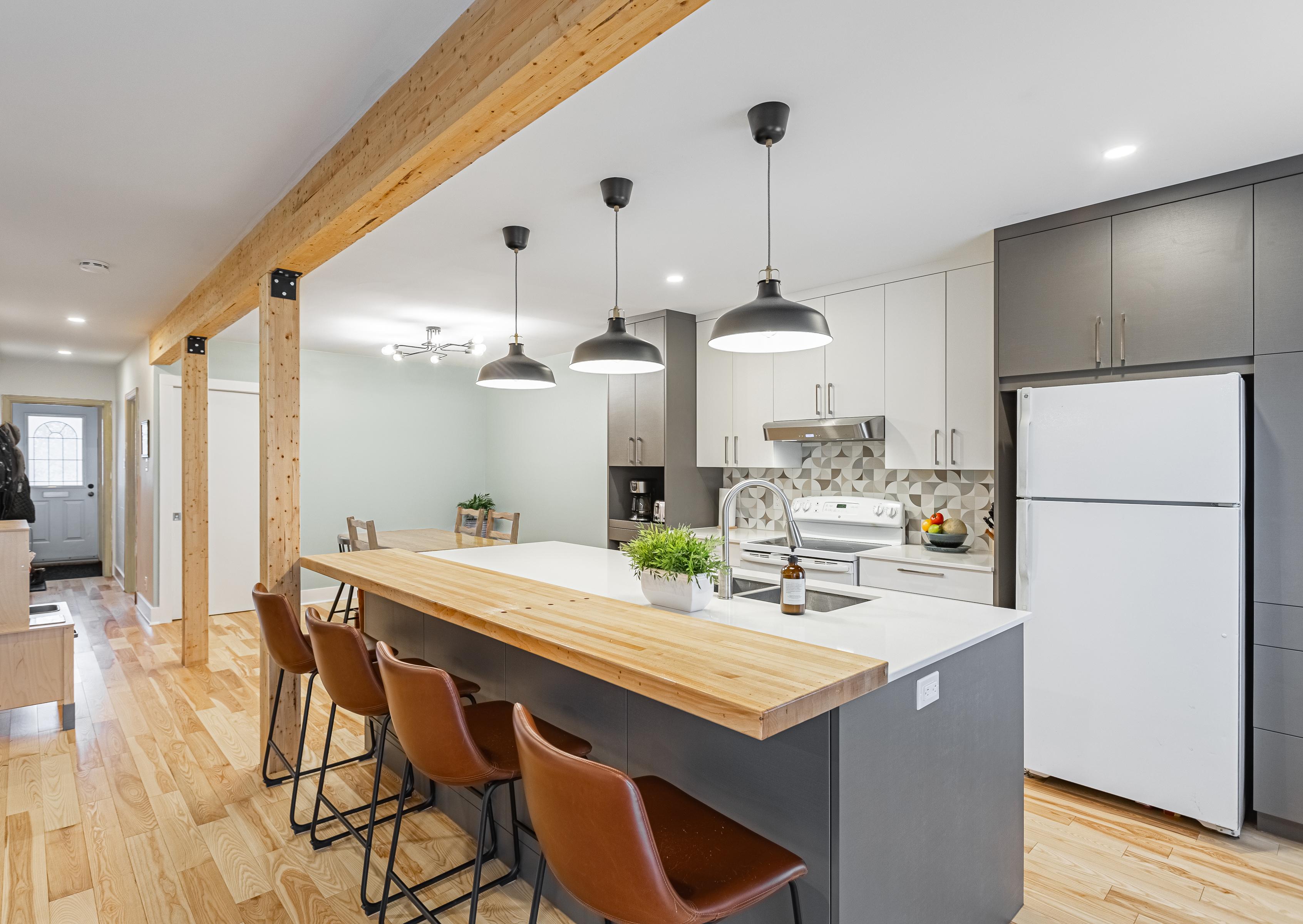 cuisine à aire ouverte avec cabinets deux tons, grand îlot et poutres en bois