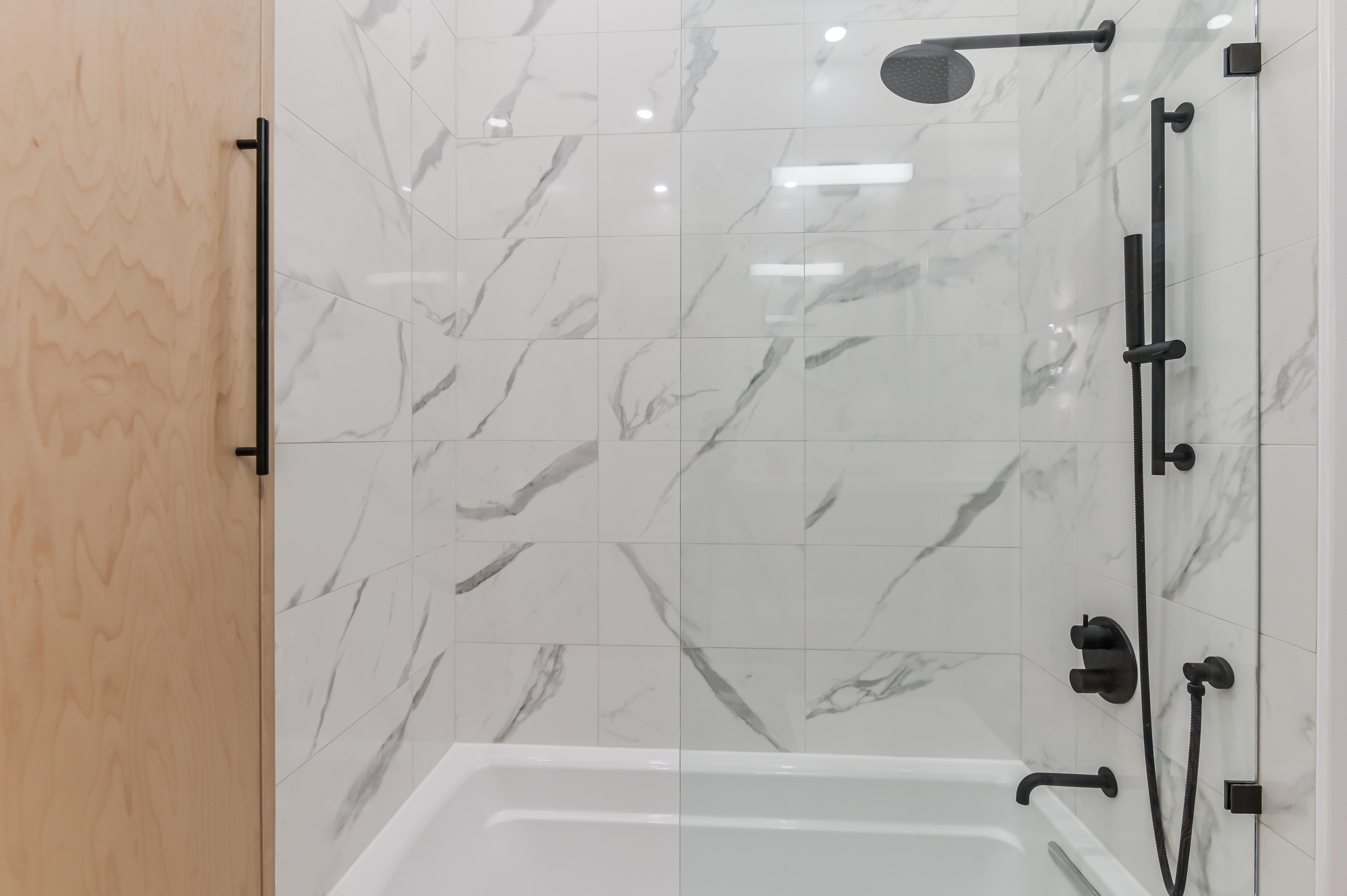 Bain-douche vitré avec tuiles façon marbre et robinetterie noire matte