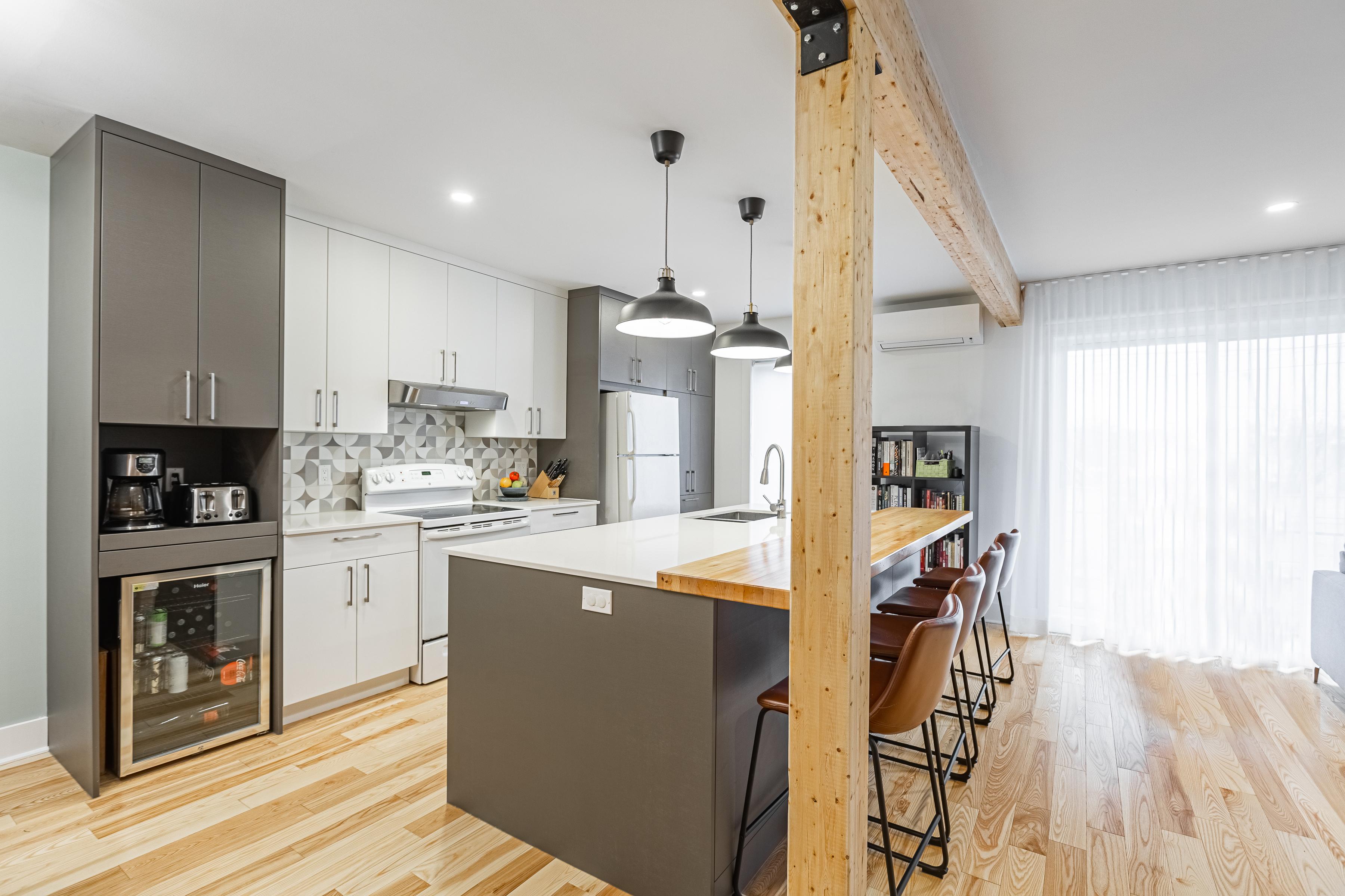 grand îlot dans une cuisine à aire ouverte moderne avec armoires blanches et grises