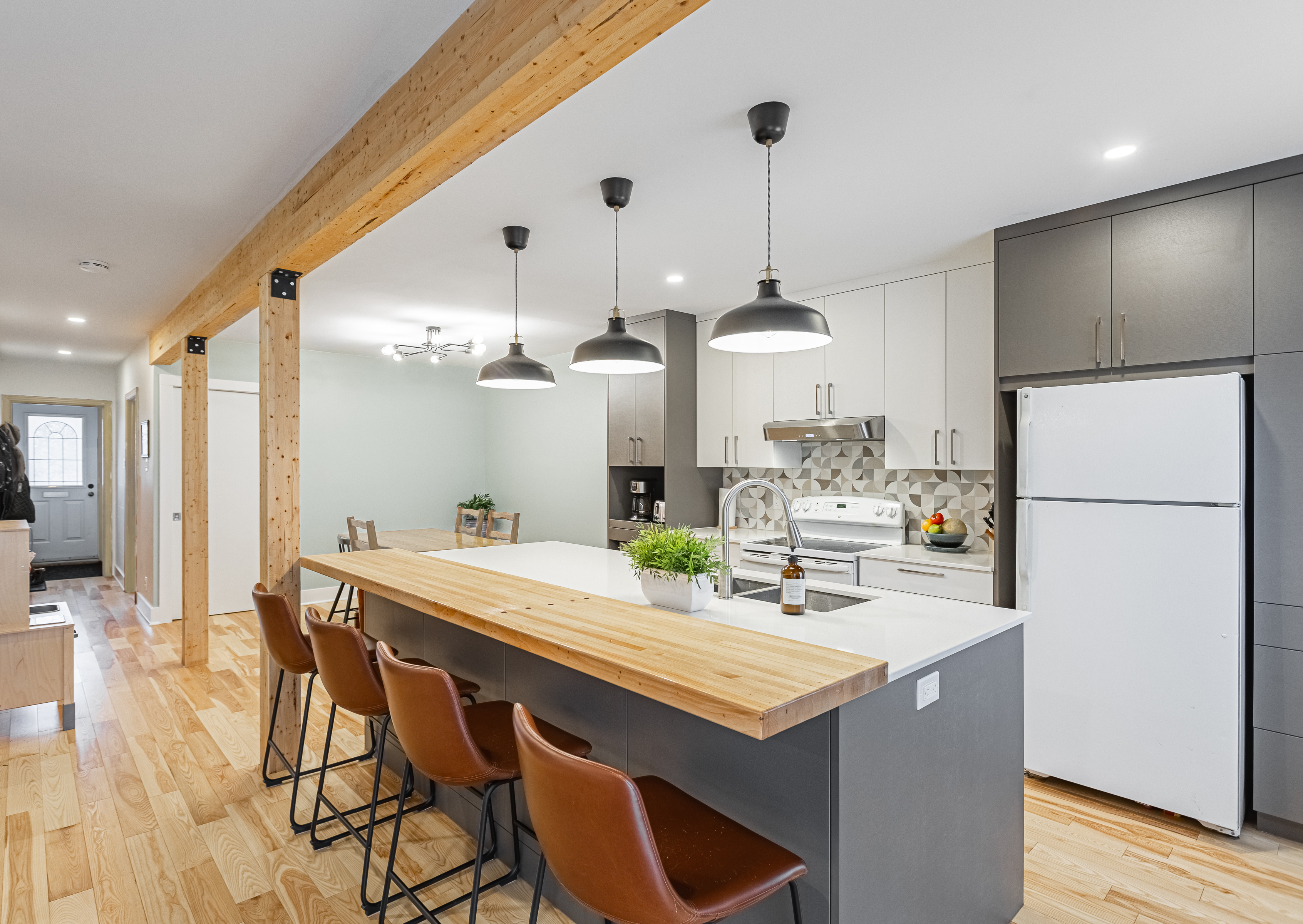 modern open concept Kitchen with two tone cabinets and white quartz countertops