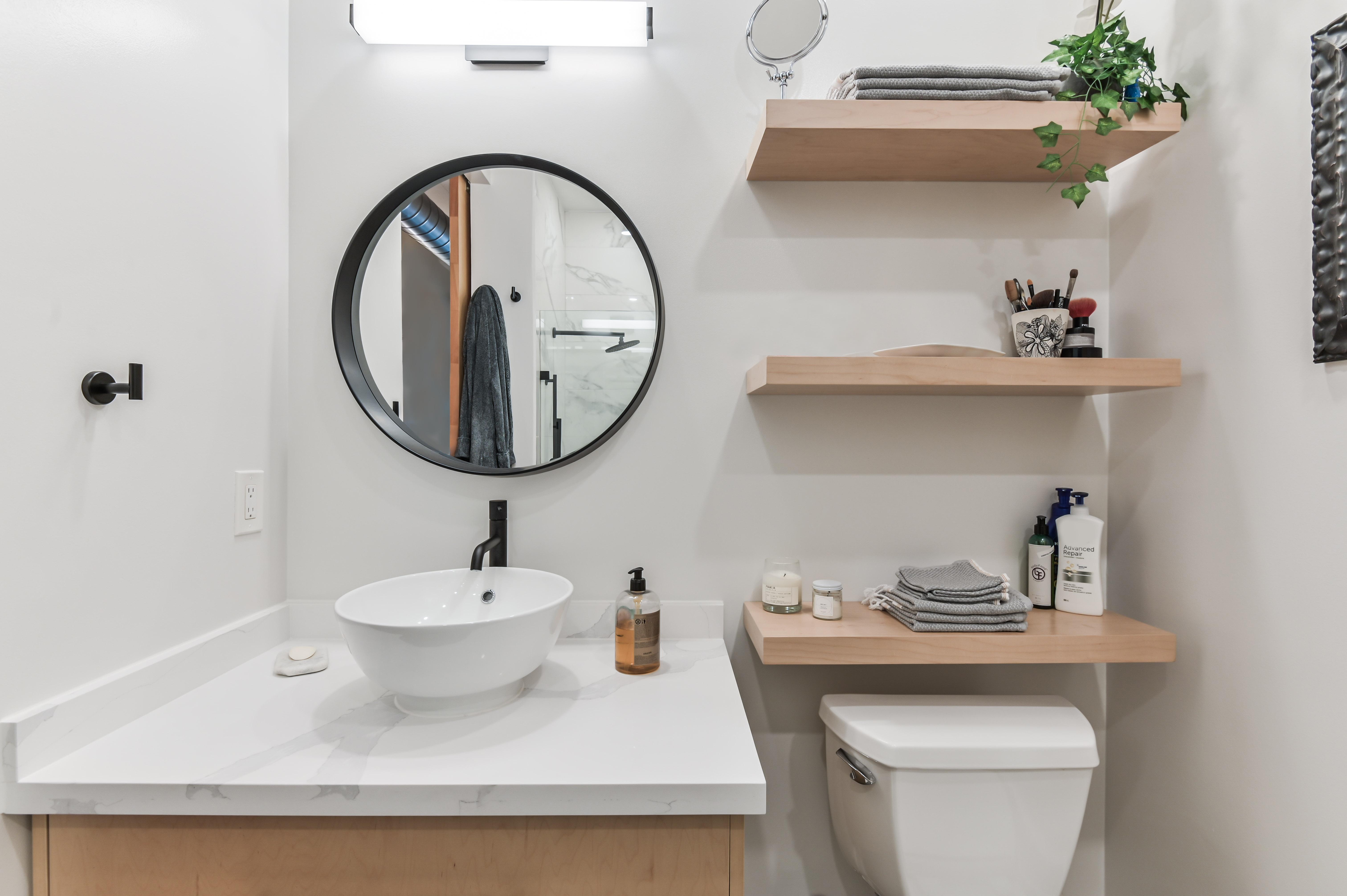 Petite salle de bain avec mobilier en bois clair, miroir rond noir et tablettes au-dessus de la toilette