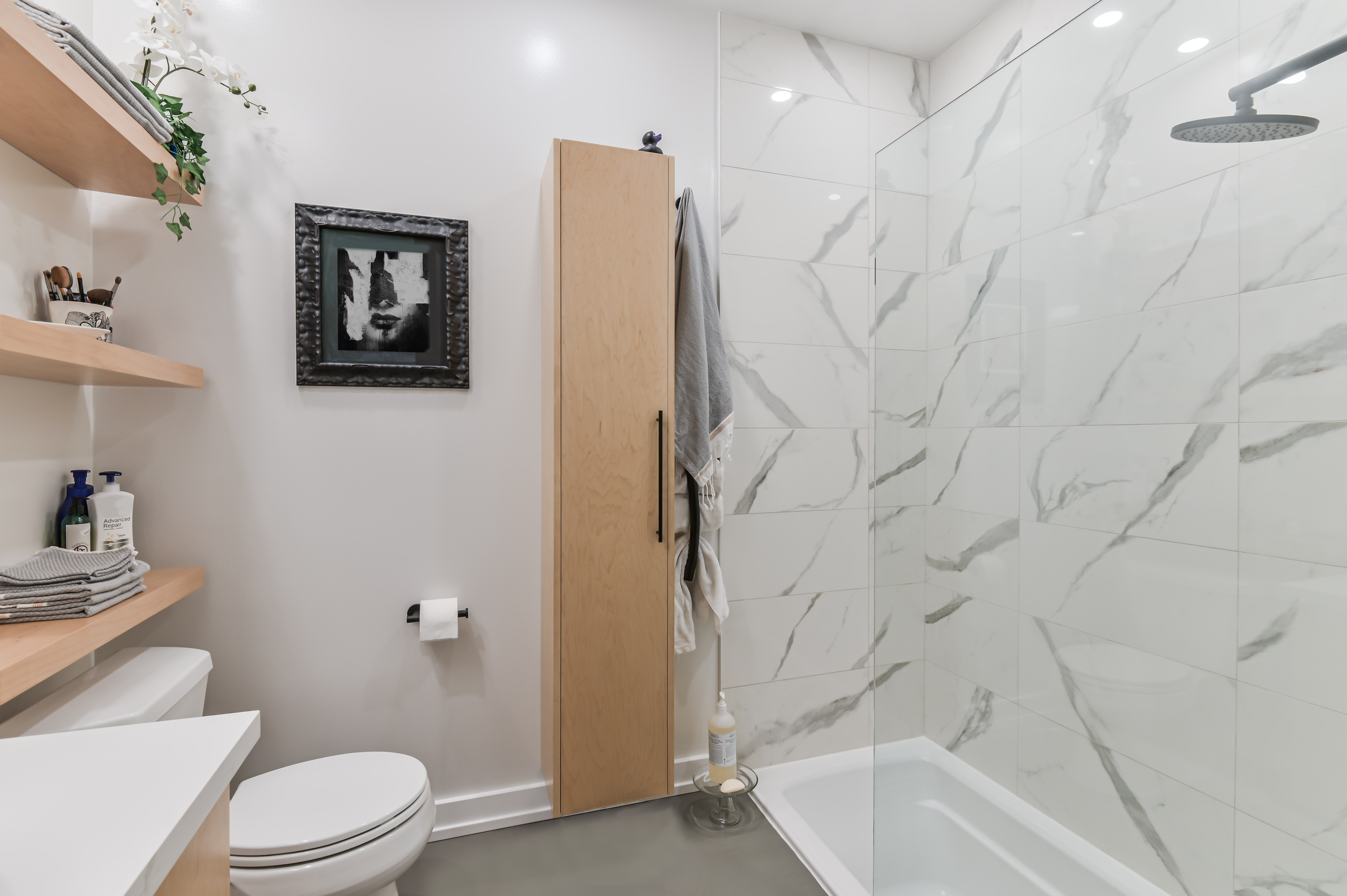 a mix of faux marbletilesand microcement,blendingbeautifullywith the rest of the new bathroomdecor