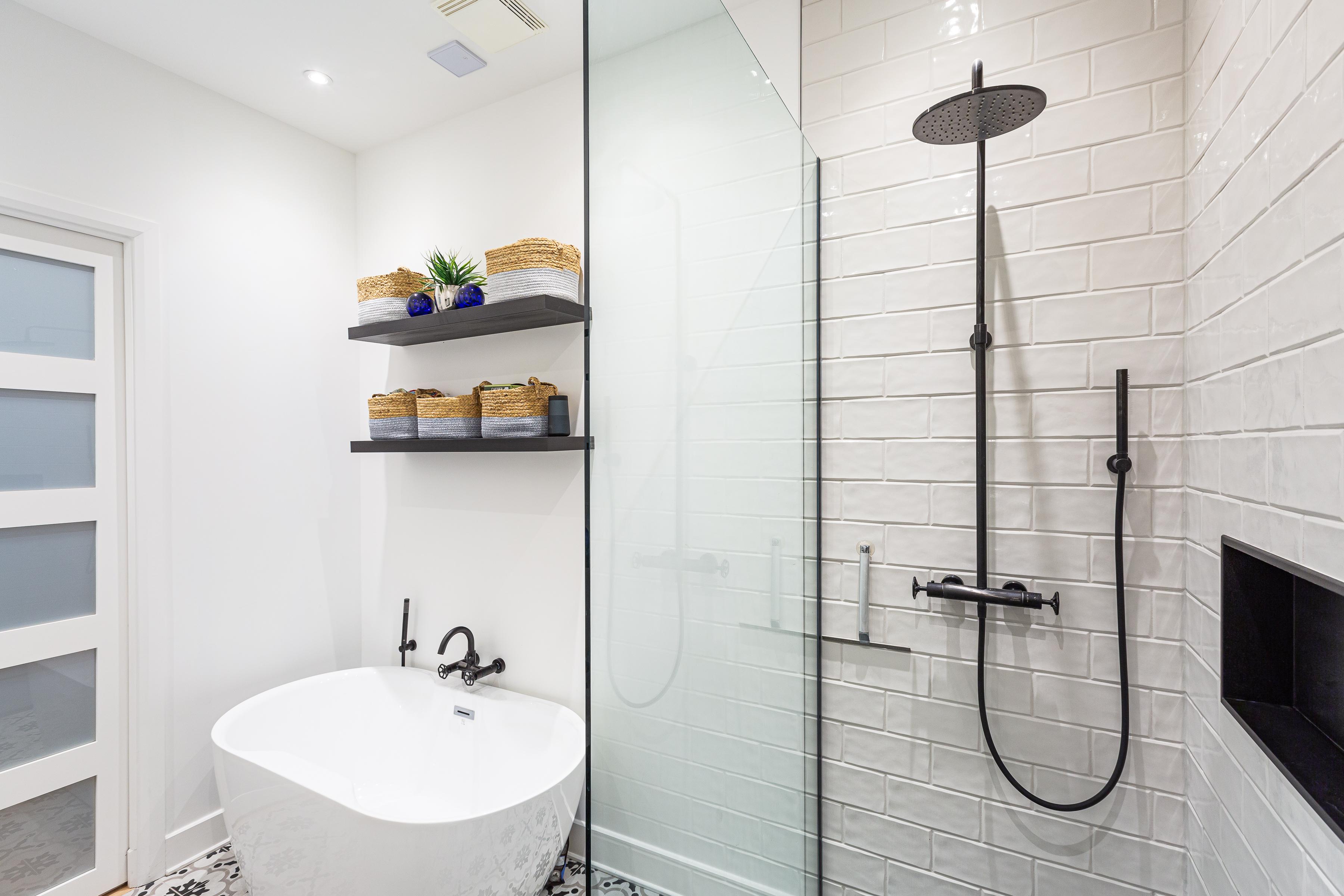 Douche ouverte avec paroi vitrée et mur en tuiles blanches