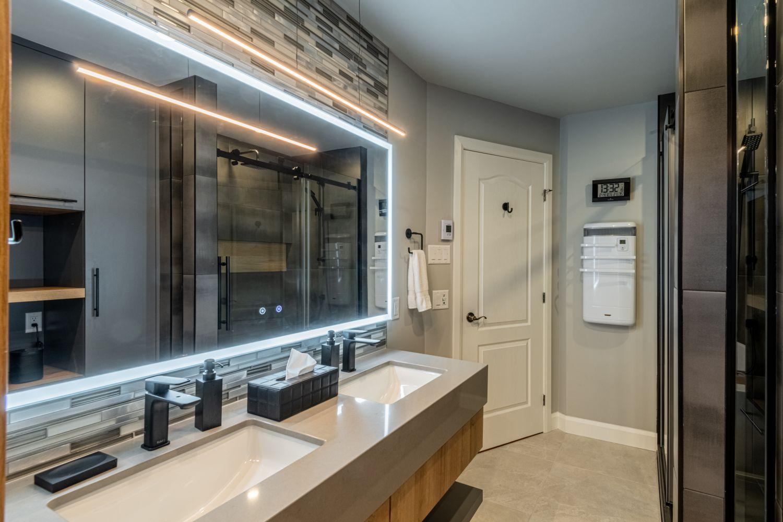 Vanité de salle de bain avec deux lavabos encastrés et miroir rétroéclairé