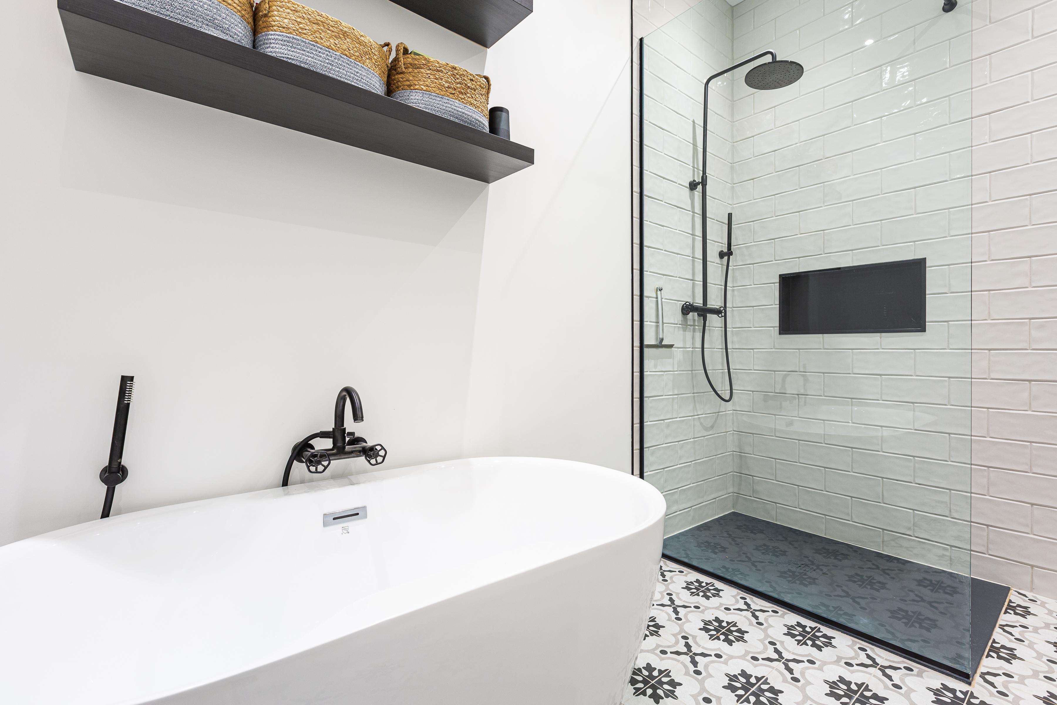 Baignoire blanche autoportante avec douche vitrée et robinetterie noire