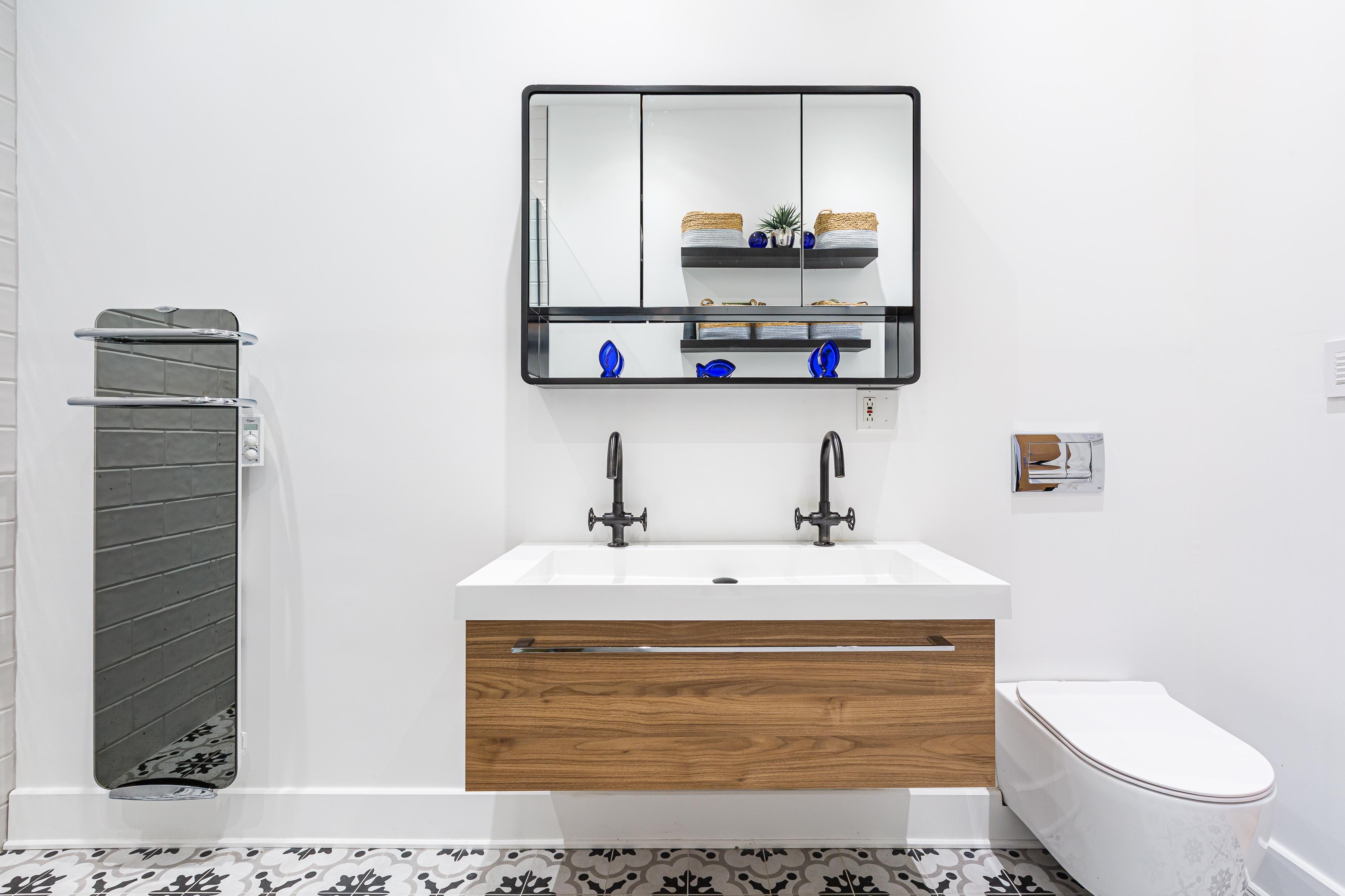 vanité de salle de bain suspendue avec robinets noirs et miroir