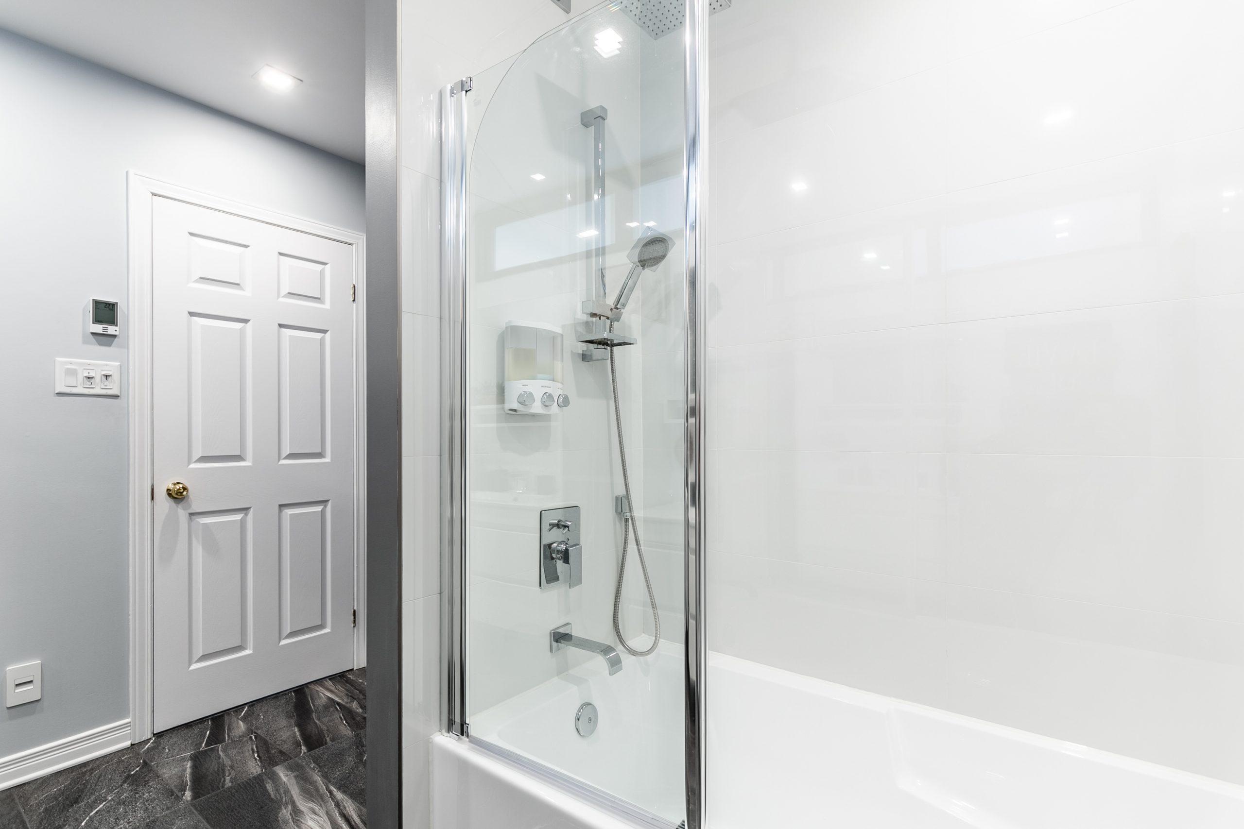 Bain-douche vitré avec une robinetterie chrome et vue sur la porte de la salle debain