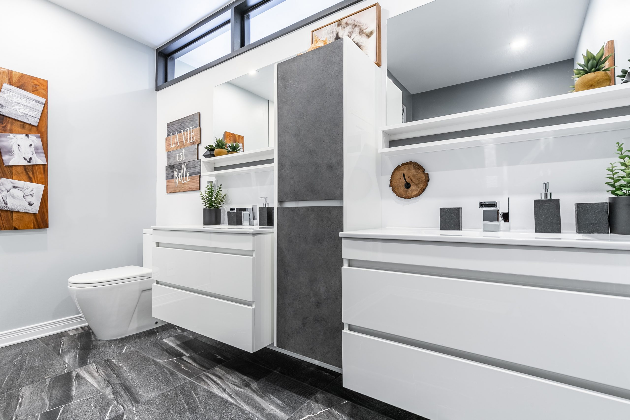 salle de bain fonctionnelle et épurée avec deux vanités blanches suspendues