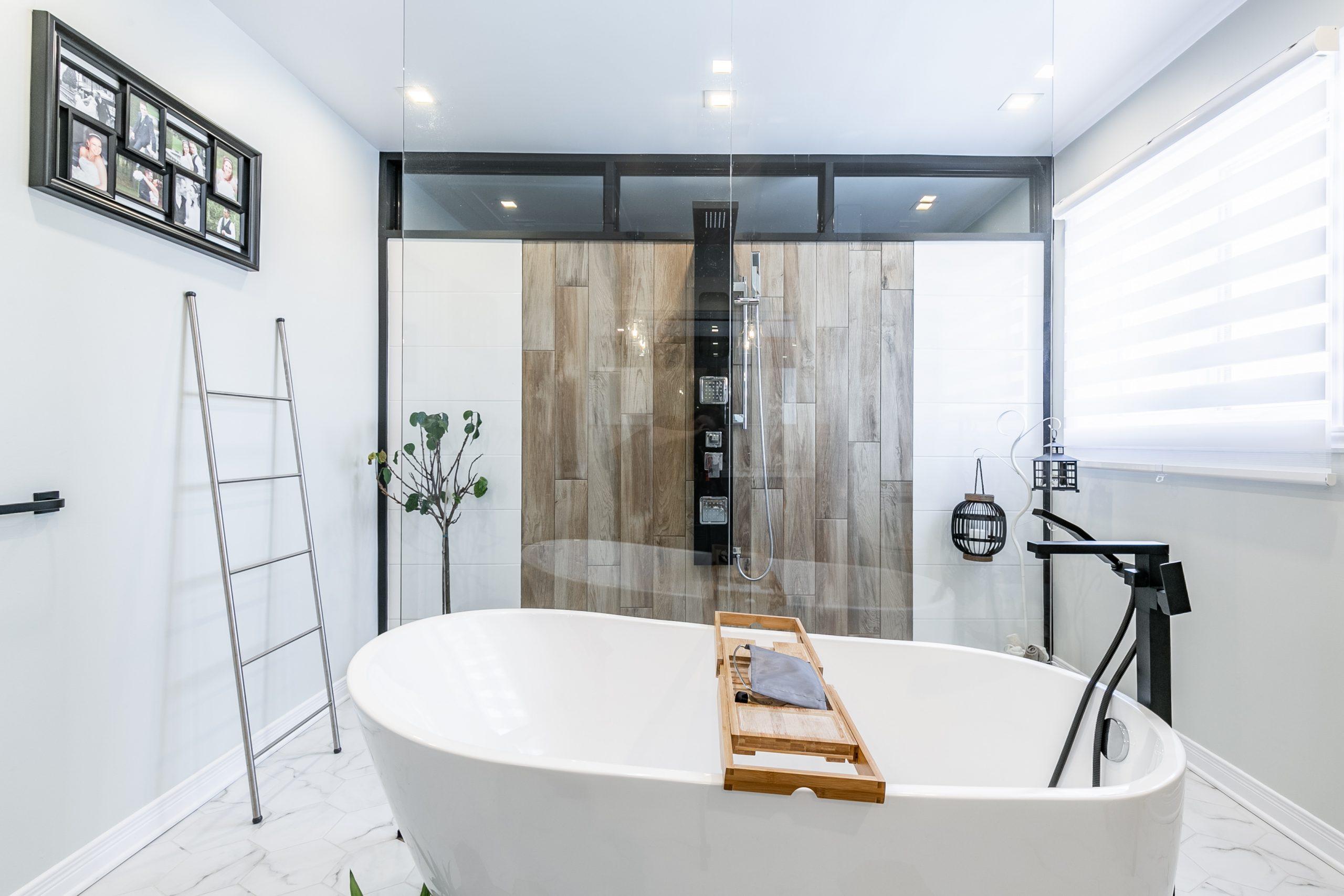 Une grande baignoire autoportante se trouve devant un panneau de verre de douche.