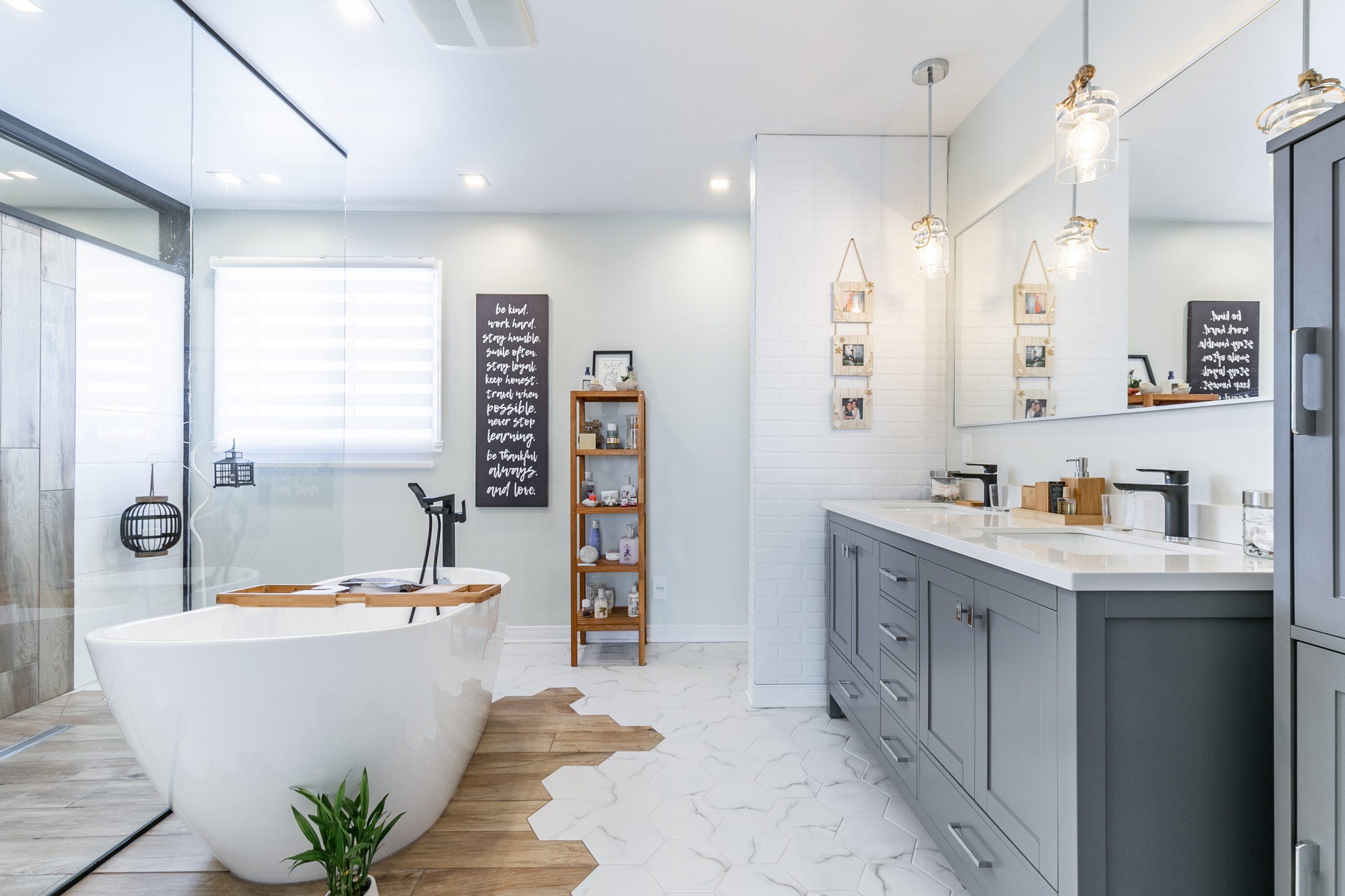 Une salle de bain avec une double vanité grise, une grande baignoire autoportante et des luminaires suspendues.