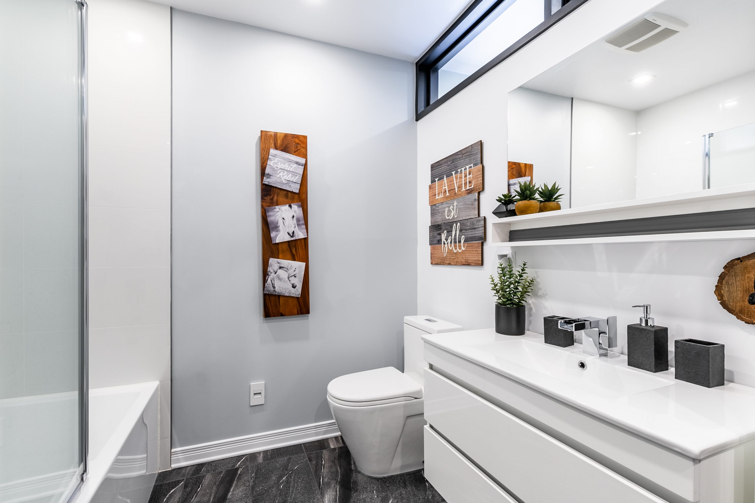 petite salle de bain fonctionnelle et épurée avec toilette et vanité blanche autoportante
