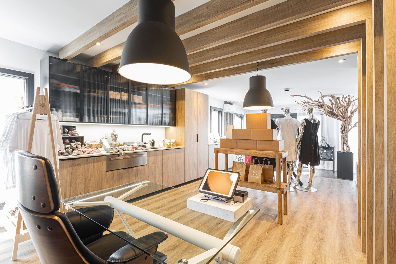 Arrière boutique avec bureau en verre, poutres en bois au plafond et luminaires industriels noirs suspendus